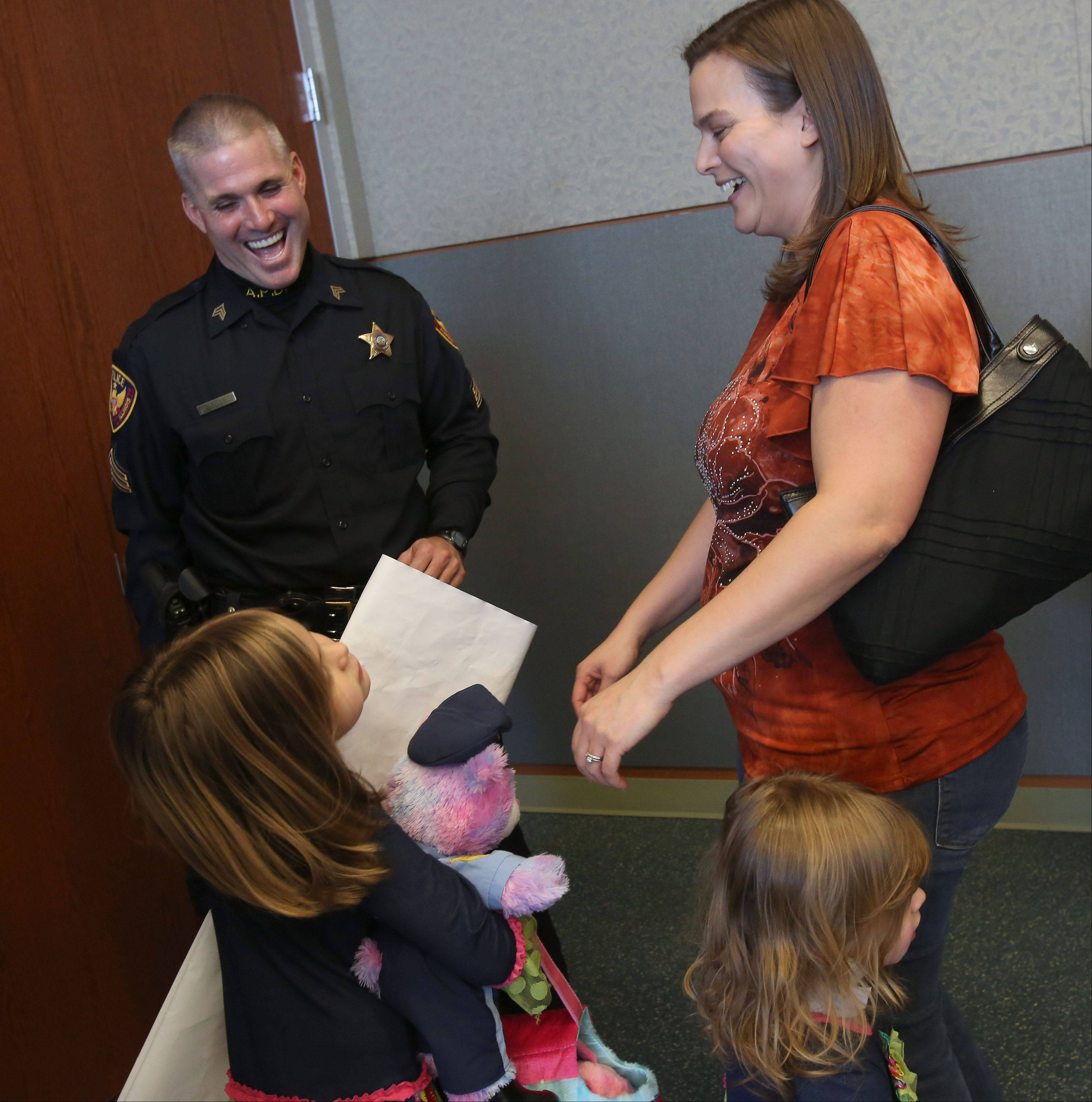 Sgt. Bill Rowley chats with Jessica Schmidt and daughters Abby, 2, and Emma, 5, at the Aurora Police Station.