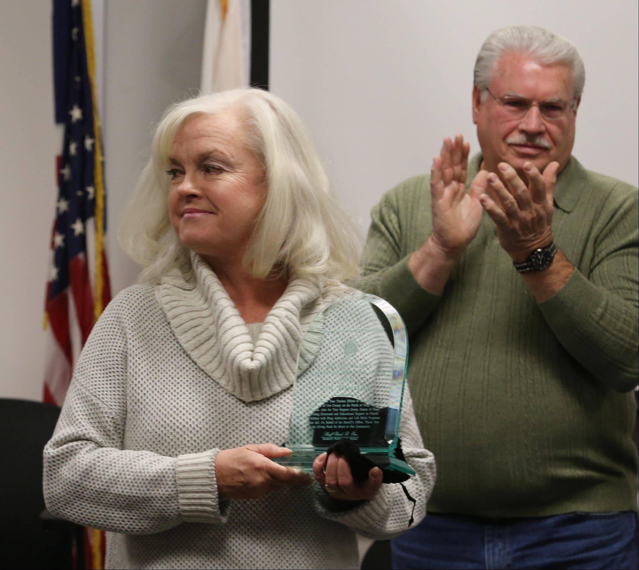Lea Minalga of St. Charles accepts her award Thursday as Richard Ebey, son of the late Roscoe Ebey, applauds in the background during the annual Roscoe Ebey Citizen of the Year ceremony at the Kane County Sheriff's Department in St. Charles. Geneva residents Lorraine Stahl and Christine Propheter also shared in the award.