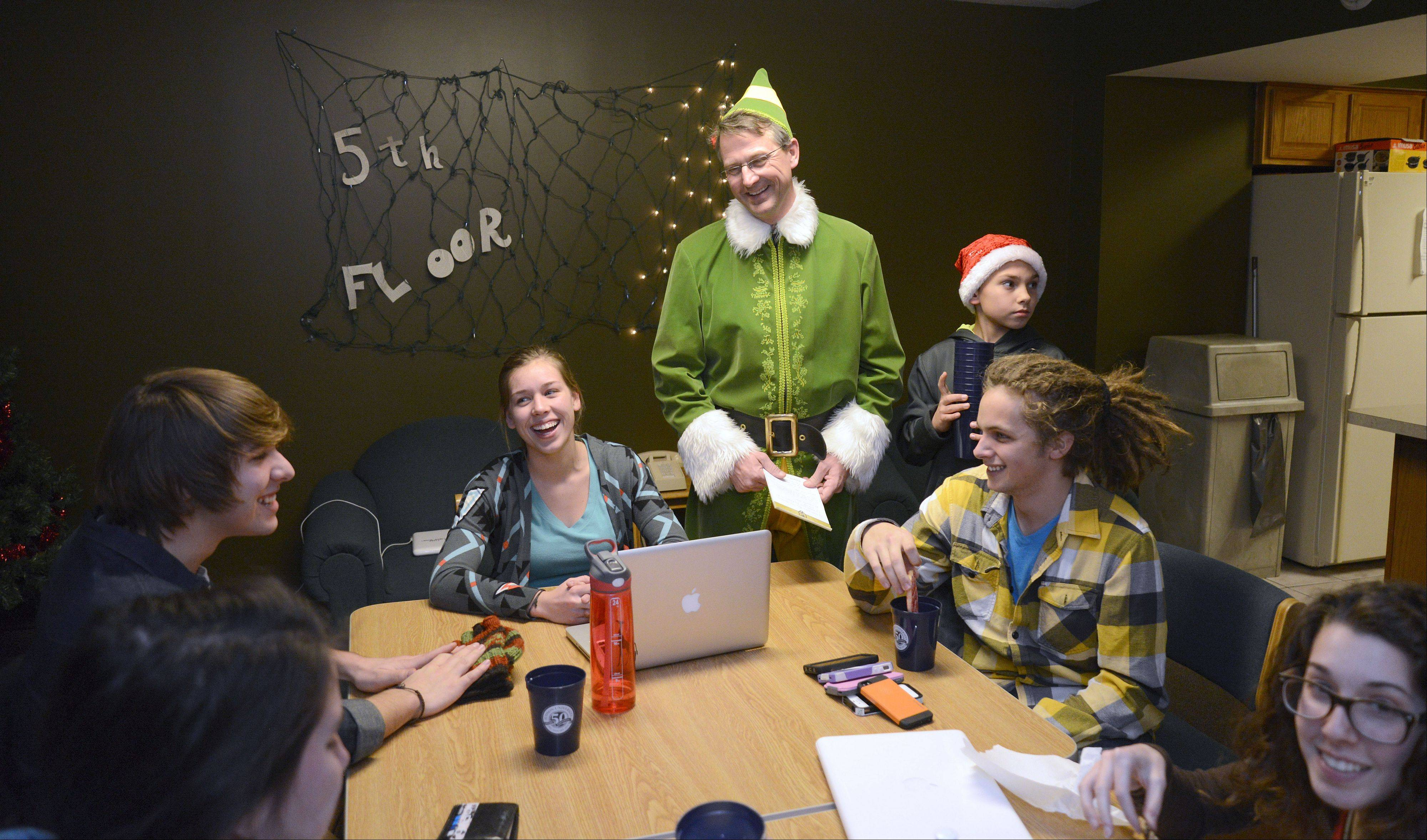 "Judson University President Gene C. Crume Jr., dressed as Buddy the Elf, has Gavin Buckland, Layne Anderson (both from Iowa) and Josh Huntington of New Jersey recite the code of elves in the Lindner Tower dorms while they enjoy milk and cookies during the annual ""Storm the Dorms"" Wednesday night."