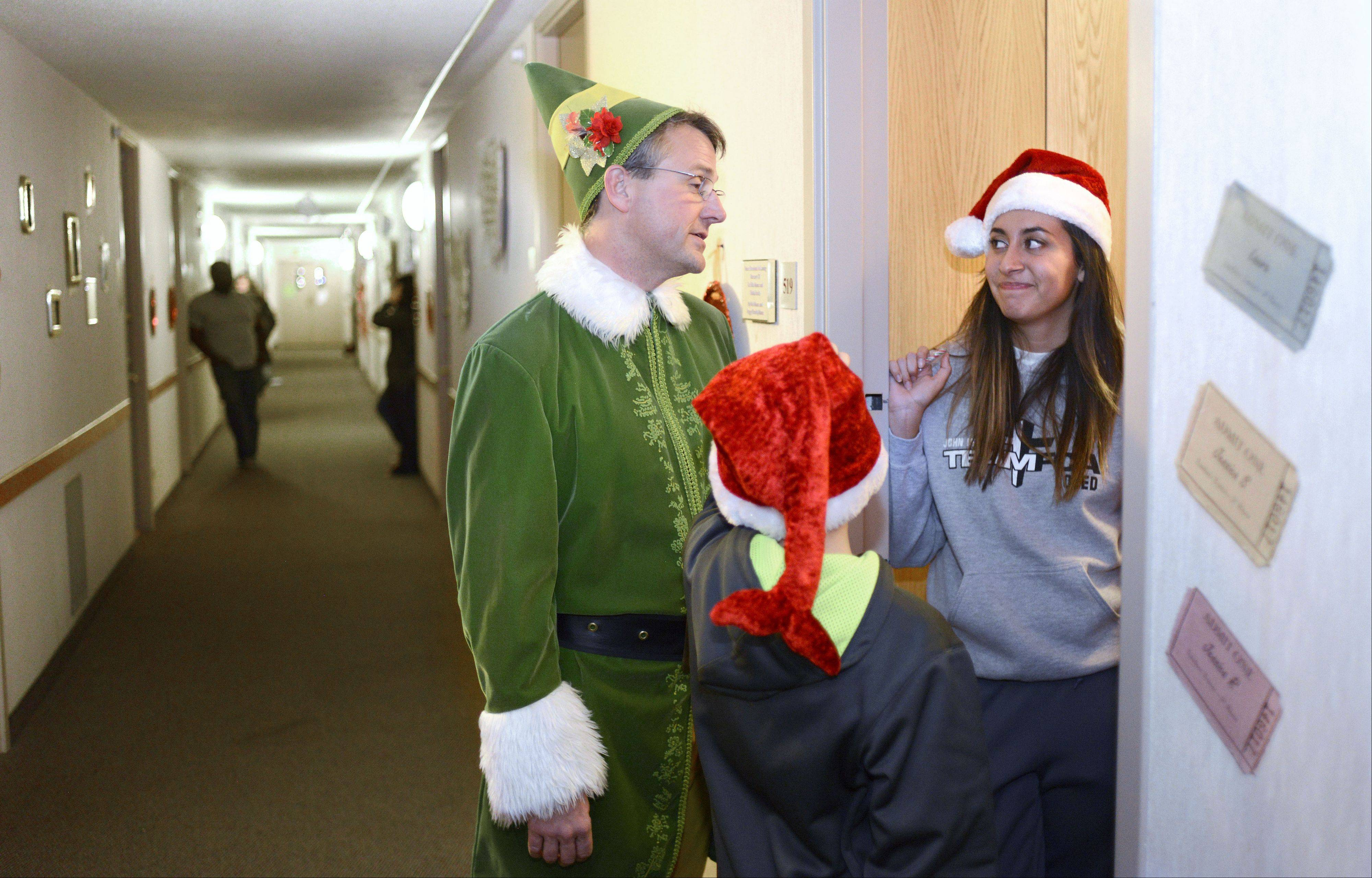 "Dressed as Buddy the Elf, Judson University President Gene C. Crume Jr. and helper Caden Pearl, 10, of Elgin, chat with Jessica Santiago of Belvidere while delivering milk, cookies and Christmas cheer to students in the Lindner Tower dorms studying for finals during the annual ""Storm the Dorms"" Wednesday night. Caden is the son of the university's softball coach, Becky Pearl."