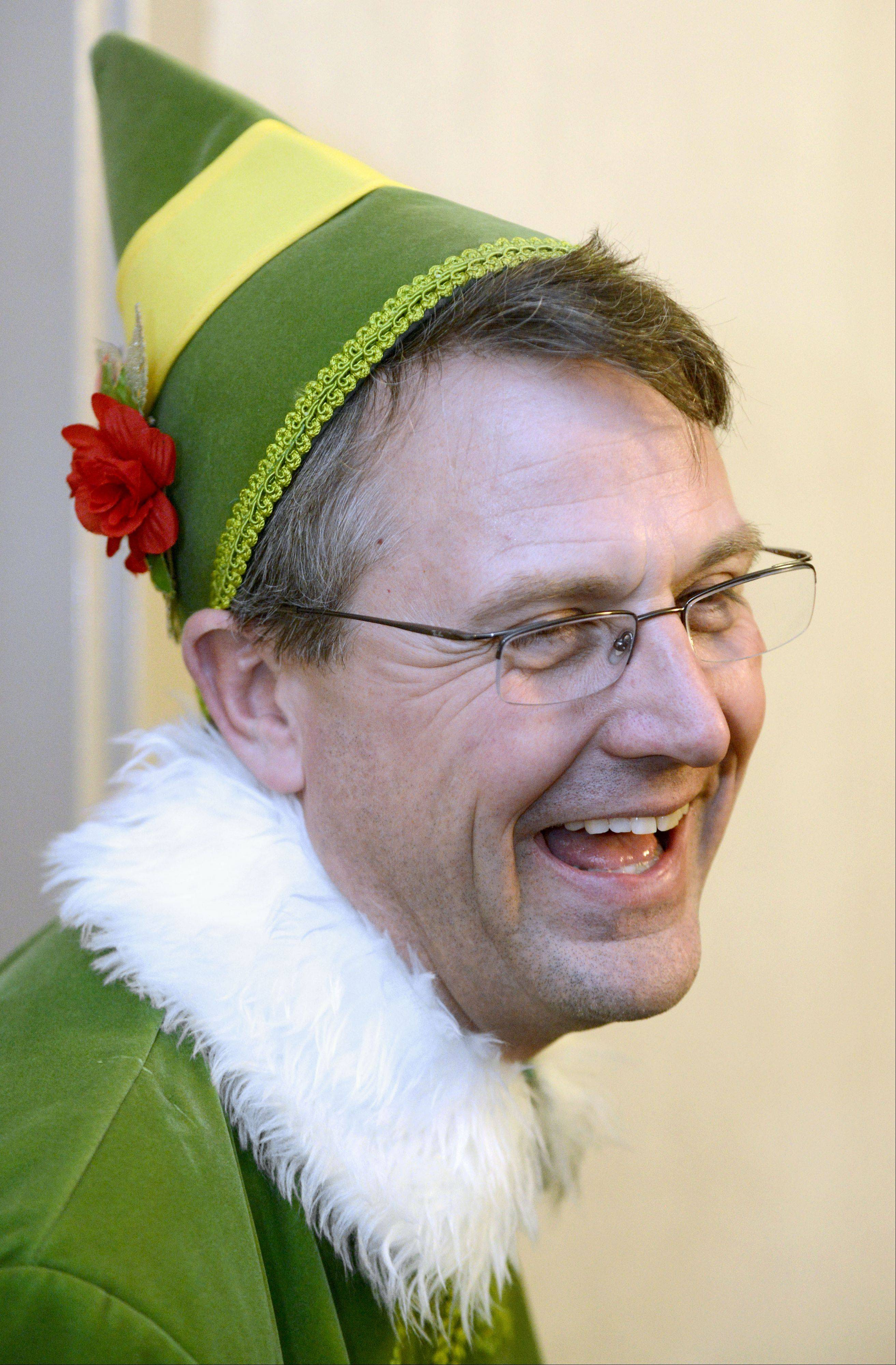 "Judson University President Gene C. Crume Jr. wears a Buddy the Elf costume while delivering food and Christmas cheer to students studying for finals during the annual ""Storm the Dorms"" Wednesday night."