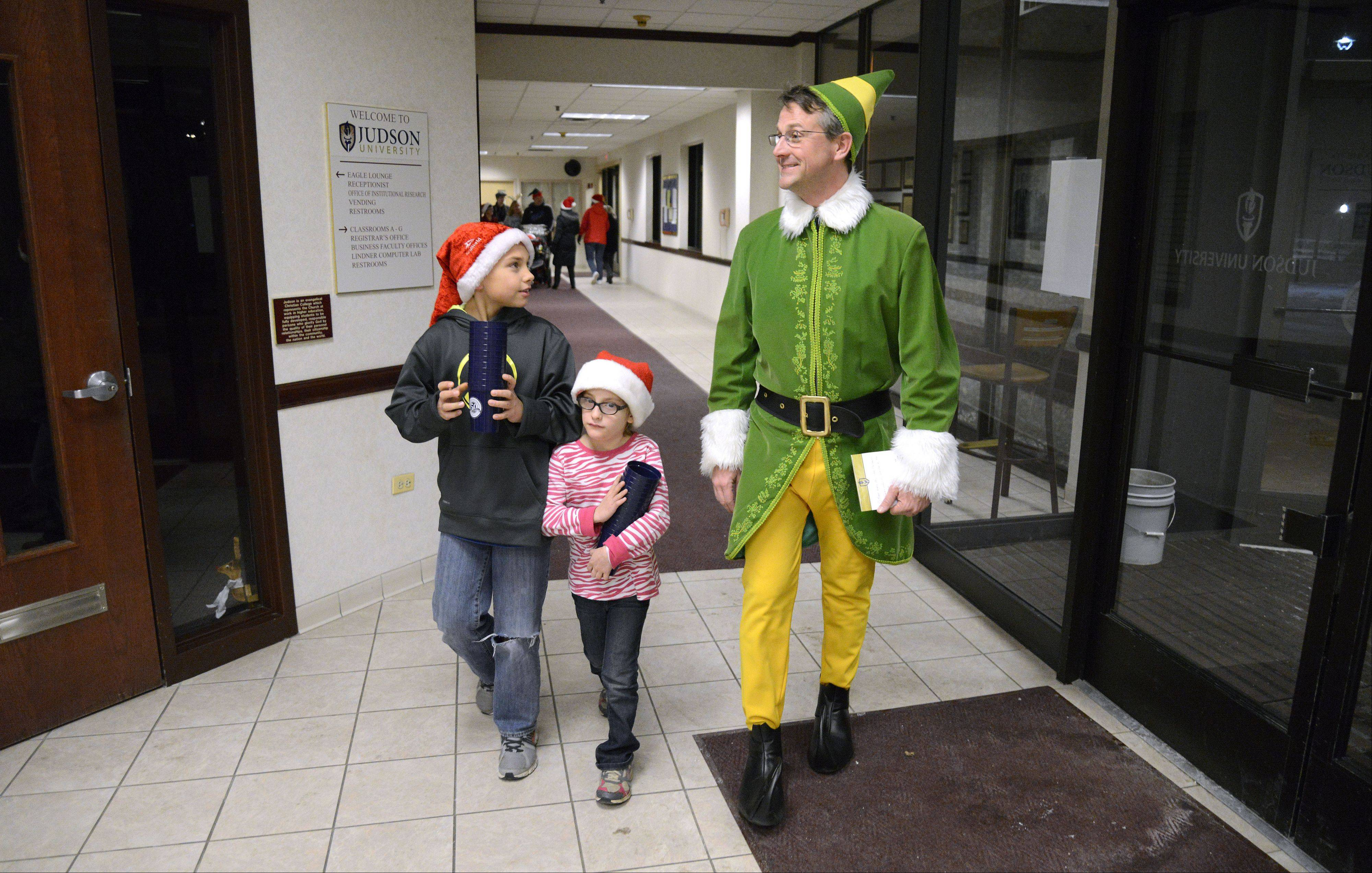 "Judson University President Gene C. Crume Jr. -- as Buddy the Elf -- and helpers Caden Pearl, 10, of Elgin and sister Allison, 7, start their trip to deliver milk and cookies to students during the annual ""Storm the Dorms"" Wednesday night."