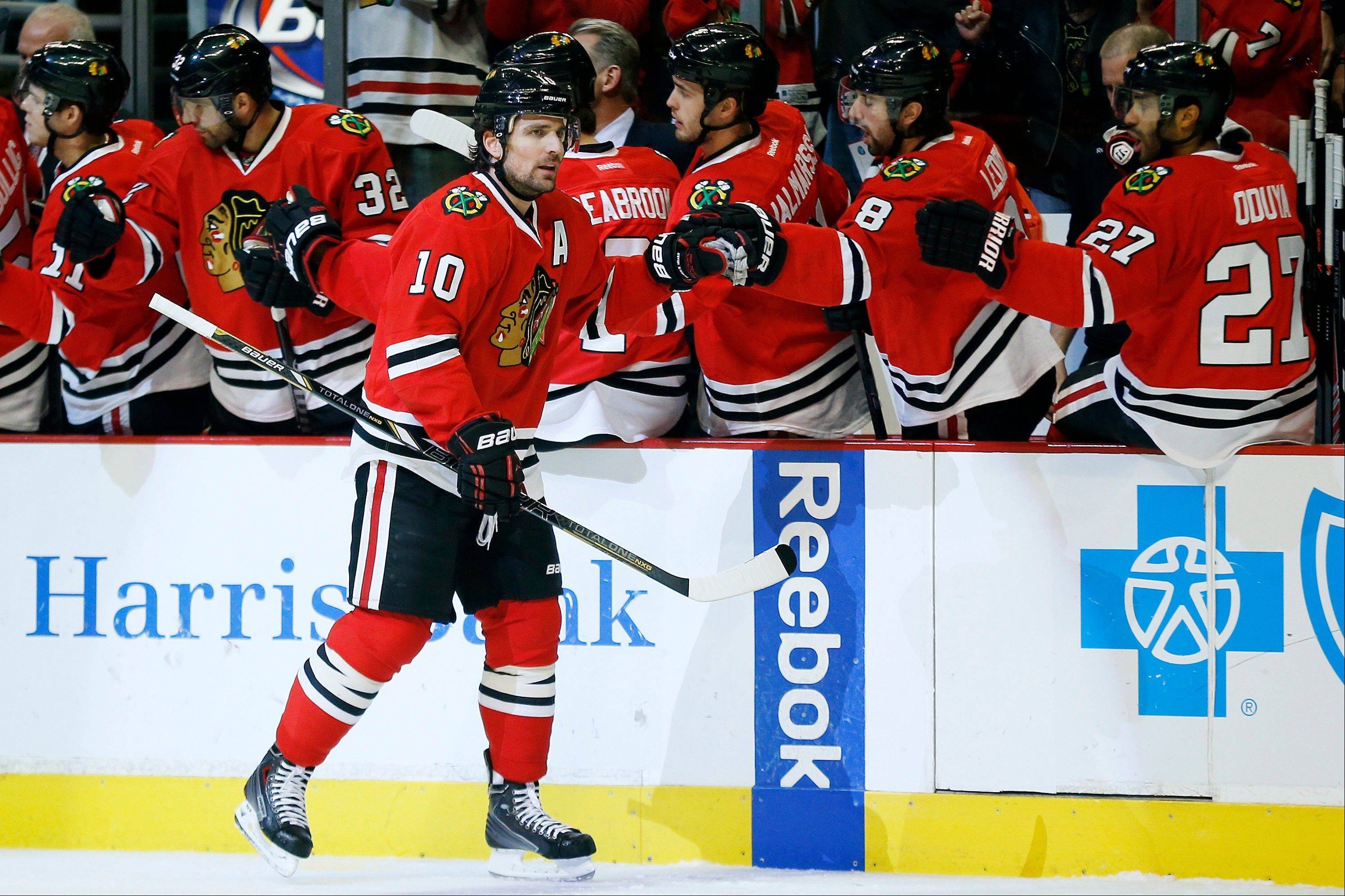 Blackhawks left wing Patrick Sharp (10) celebrates with teammates after scoring a goal against the Florida Panthers during the first period of an NHL hockey game on Sunday, Dec. 8, 2013, in Chicago.