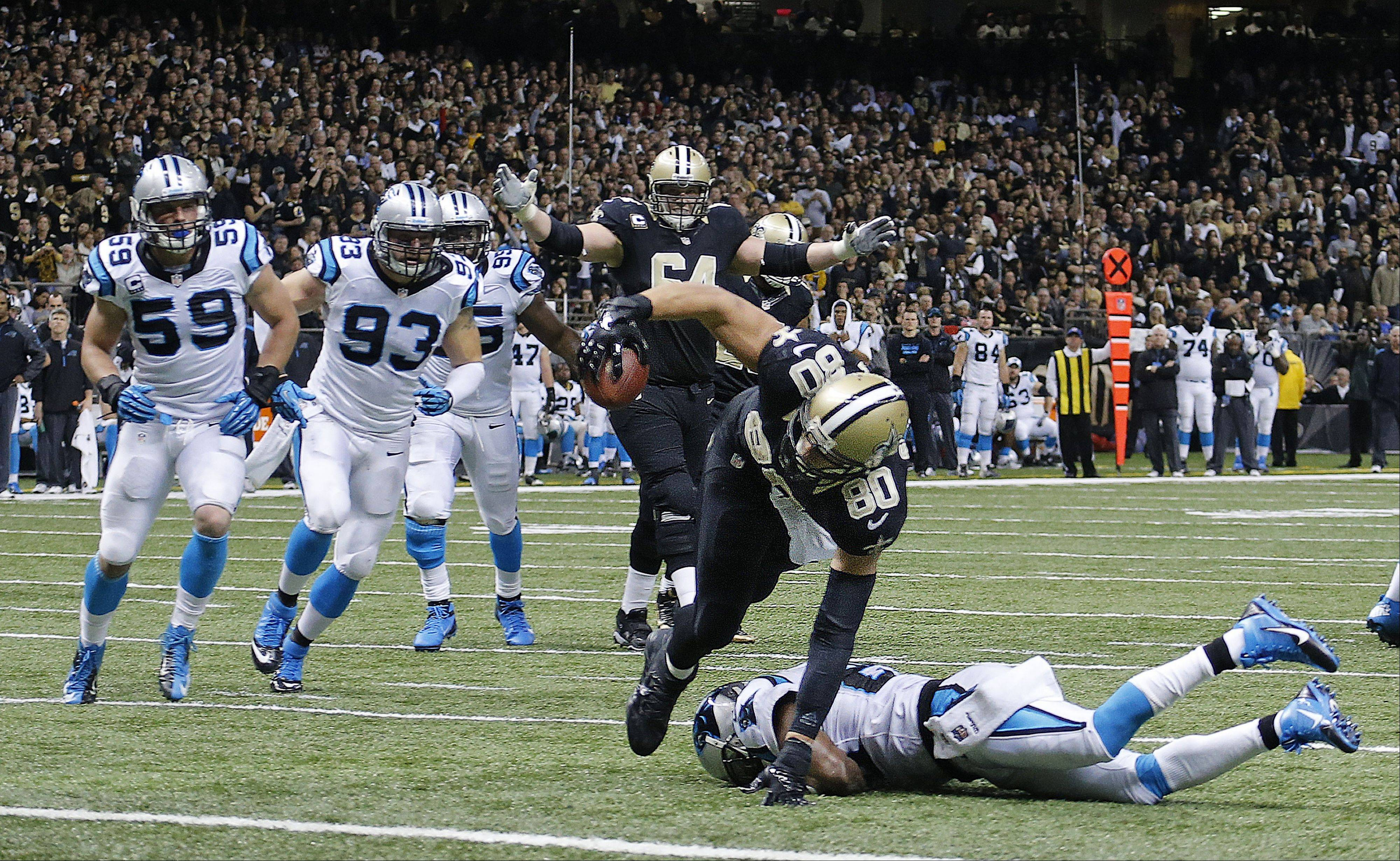 New Orleans Saints tight end Jimmy Graham (80) scores on a touchdown as Carolina Panthers cornerback Drayton Florence tries to tackle in the second half of an NFL football game in New Orleans, Sunday, Dec. 8, 2013.