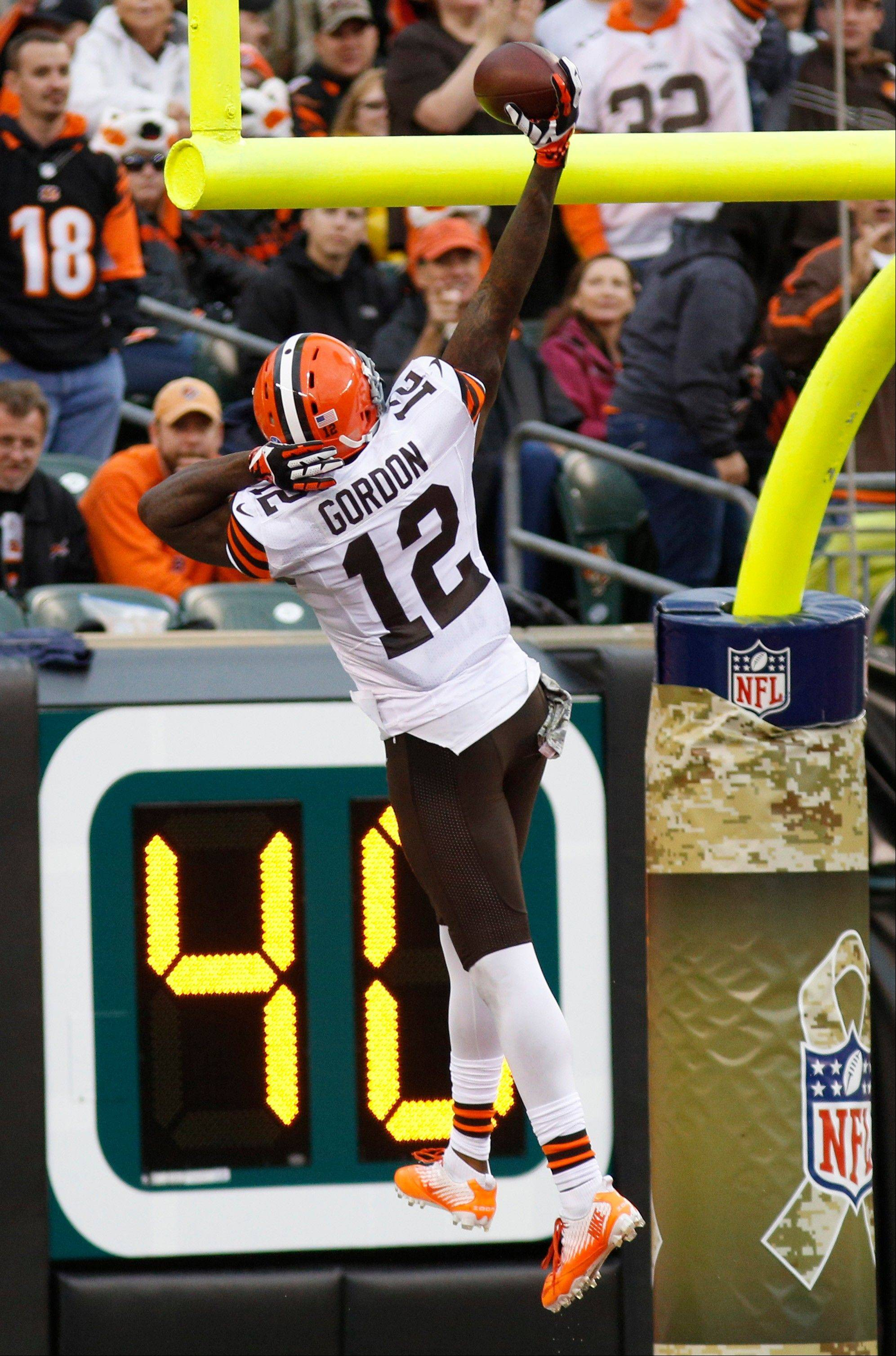 Cleveland Browns wide receiver Josh Gordon (12) spikes the ball over the goalpost after scoring on a 74-yard pass reception against the Cincinnati Bengals in the second half of an NFL football game on Sunday, Nov. 17, 2013, in Cincinnati.