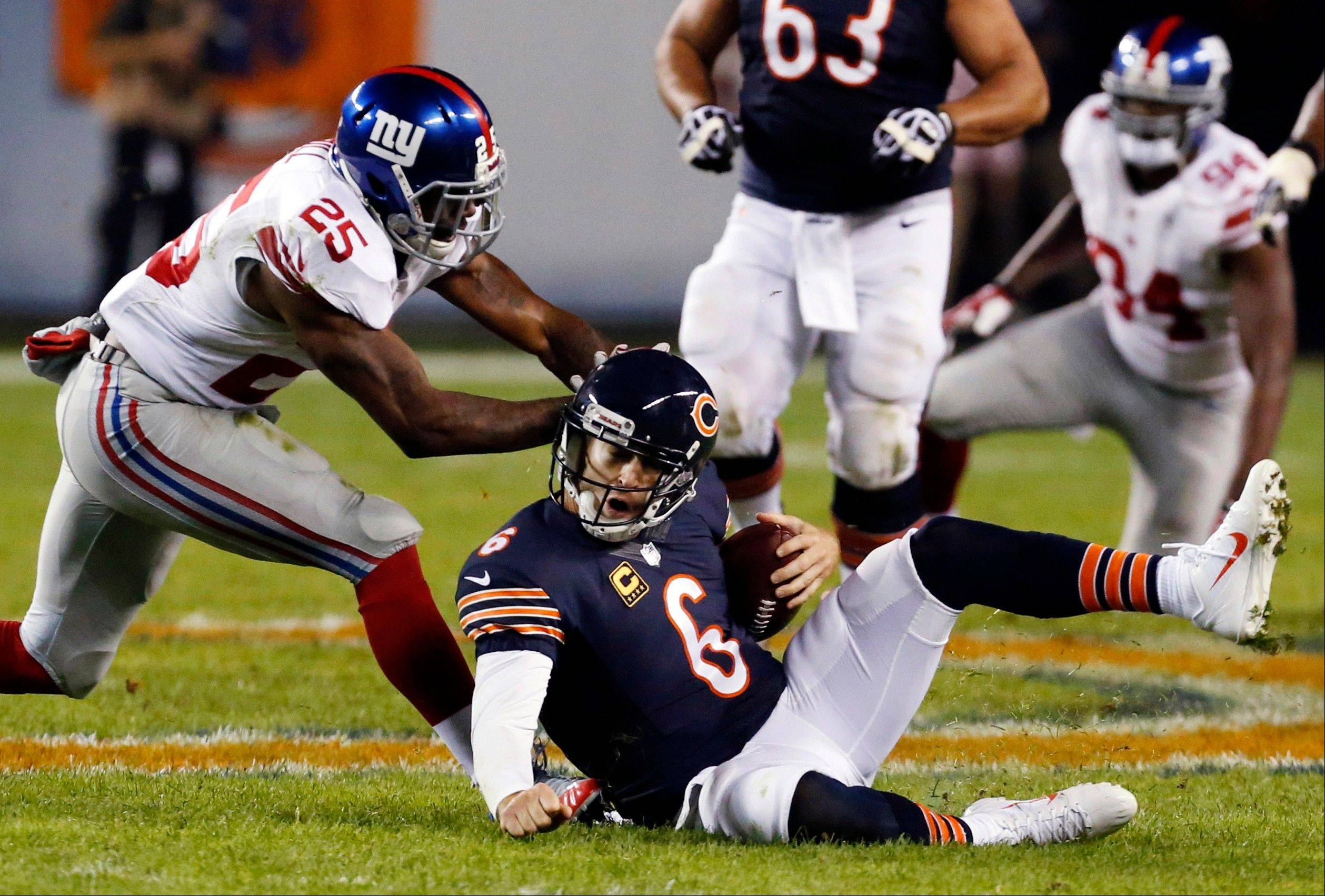 In this Oct. 10, 2013, file photo, New York Giants safety Antrel Rolle (26) pushes on the helmet of Chicago Bears quarterback Jay Cutler (6) during the second half of an NFL football game in Chicago. Rolle was penalized 15-yards for unnecessary roughness on the play. Almost once a game, an NFL player absorbs an illegal blow to the head or neck that could put his career, or worse, at risk. The NFL has been trying to prevent such blows over the past four years, targeting improper technique and making it a point of emphasis to penalize and fine players for hits that leave themselves and their opponents vulnerable.