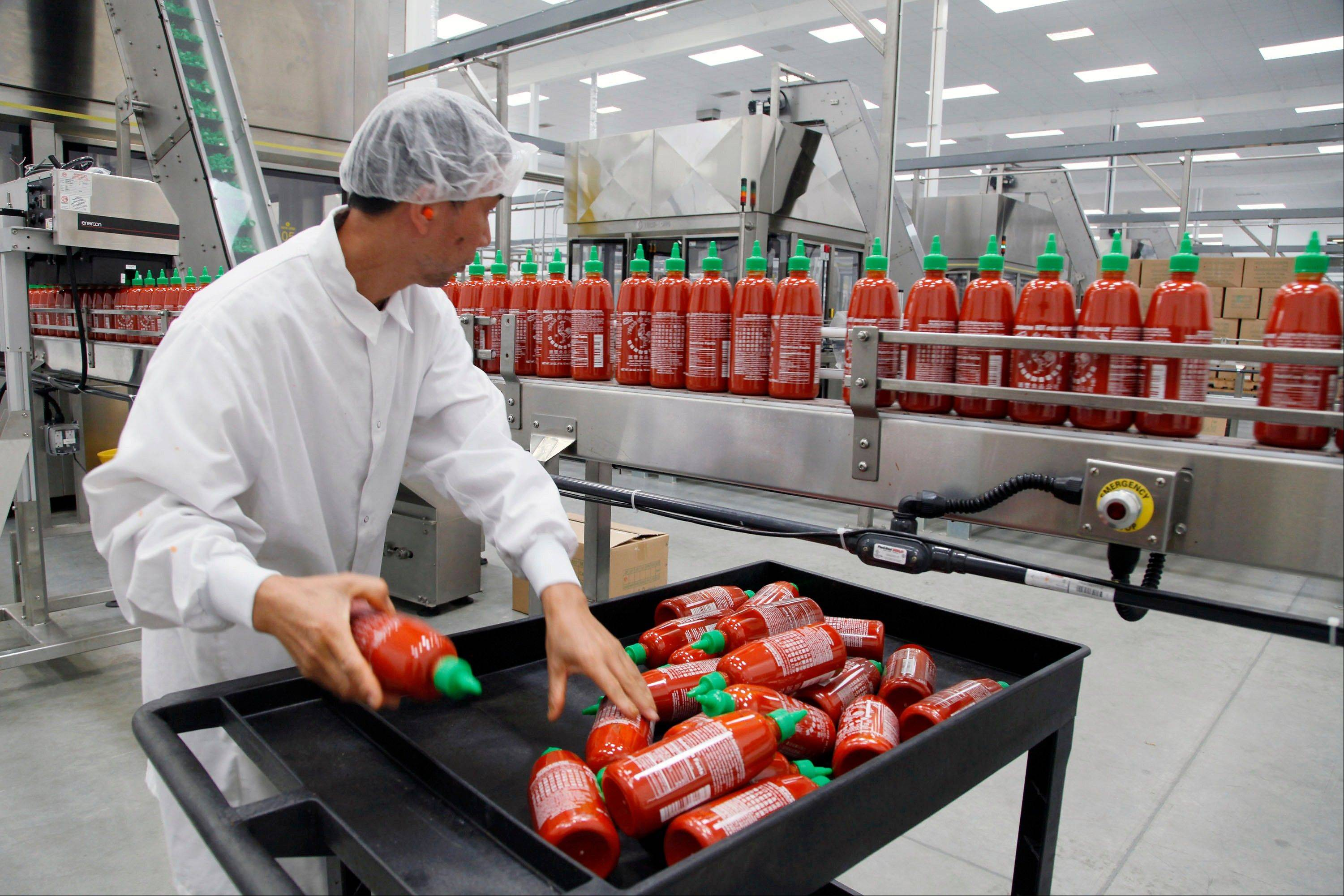 Sriracha chili sauce is produced at the Huy Fong Foods factory in Irwindale, Calif. The Commerce Department reported Friday that high unemployment and weak wage increases have made it difficult for businesses to raise prices.