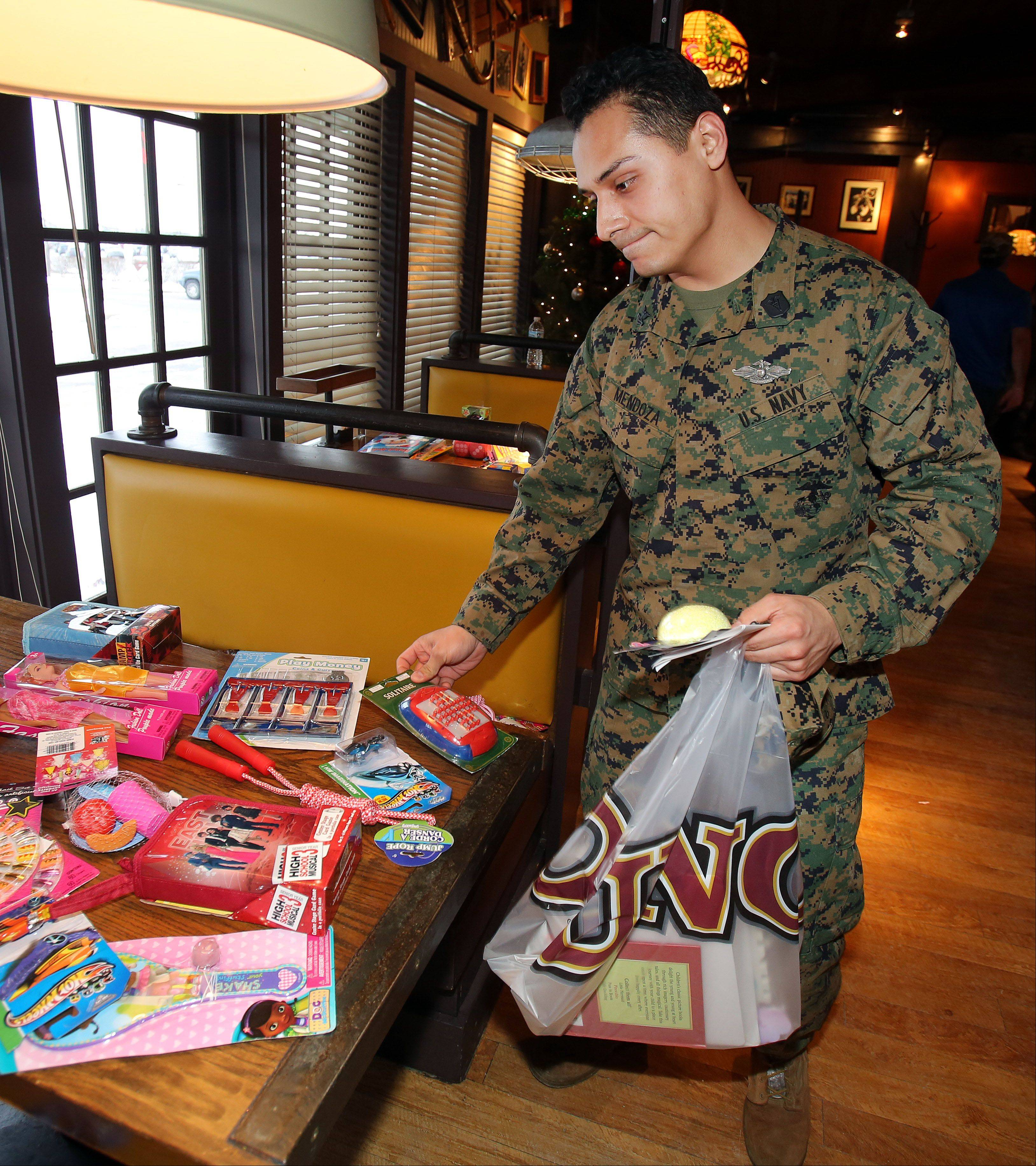 Marco Mendoza, of Great Lakes Naval Station, looks through toys for his children during the Operation Homefront Illinois toy drive event Friday in Gurnee. The group supplied holiday toys to children of military personnel at Uno Chicago Grill.