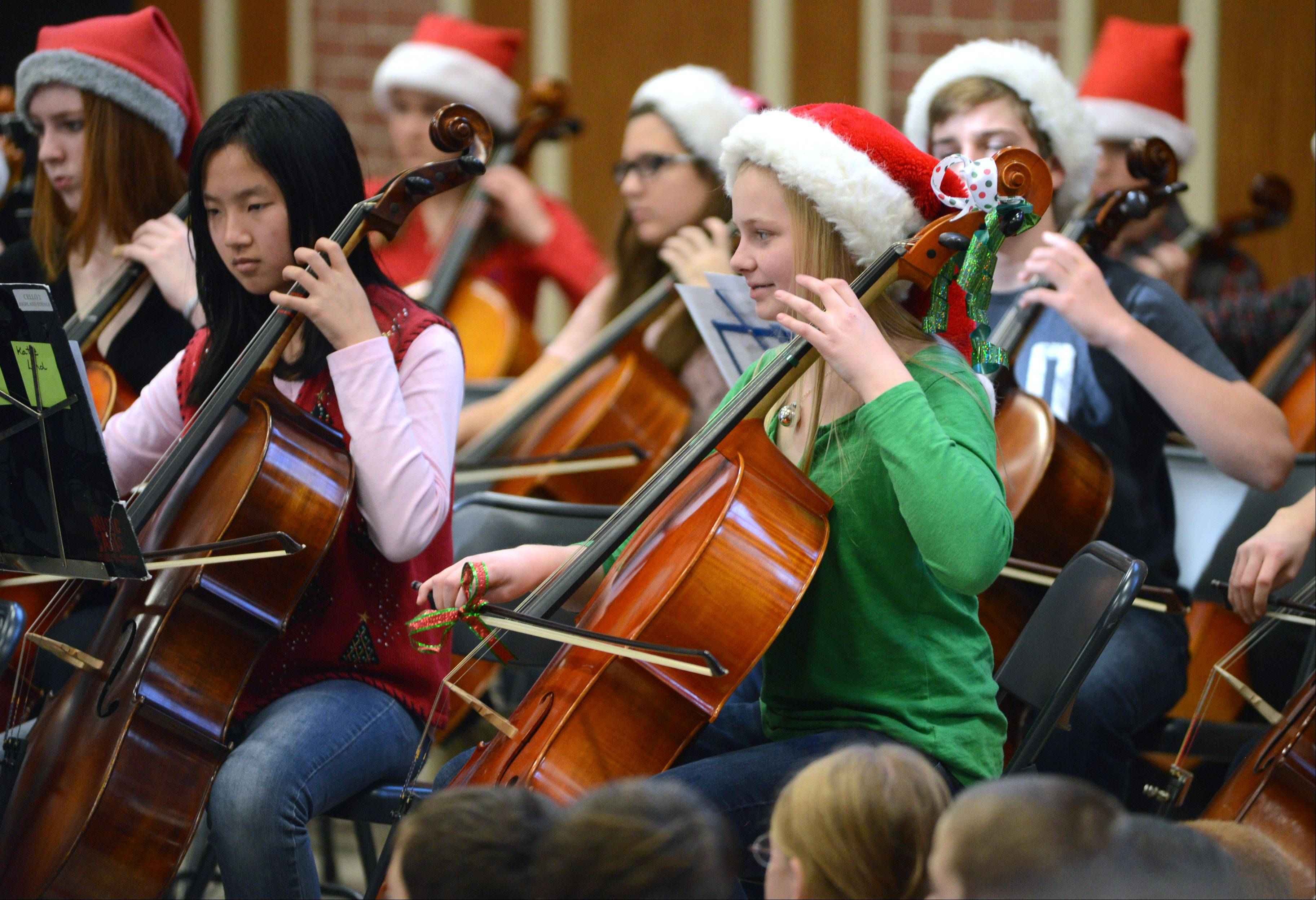 Highland Symphonic Orchestra cello player Katie Lund, right, plays seasonal favorites with fellow musicians Friday at Copeland Manor Elementary School in Libertyville. The group played at all four Libertyville District 70 elementary schools.