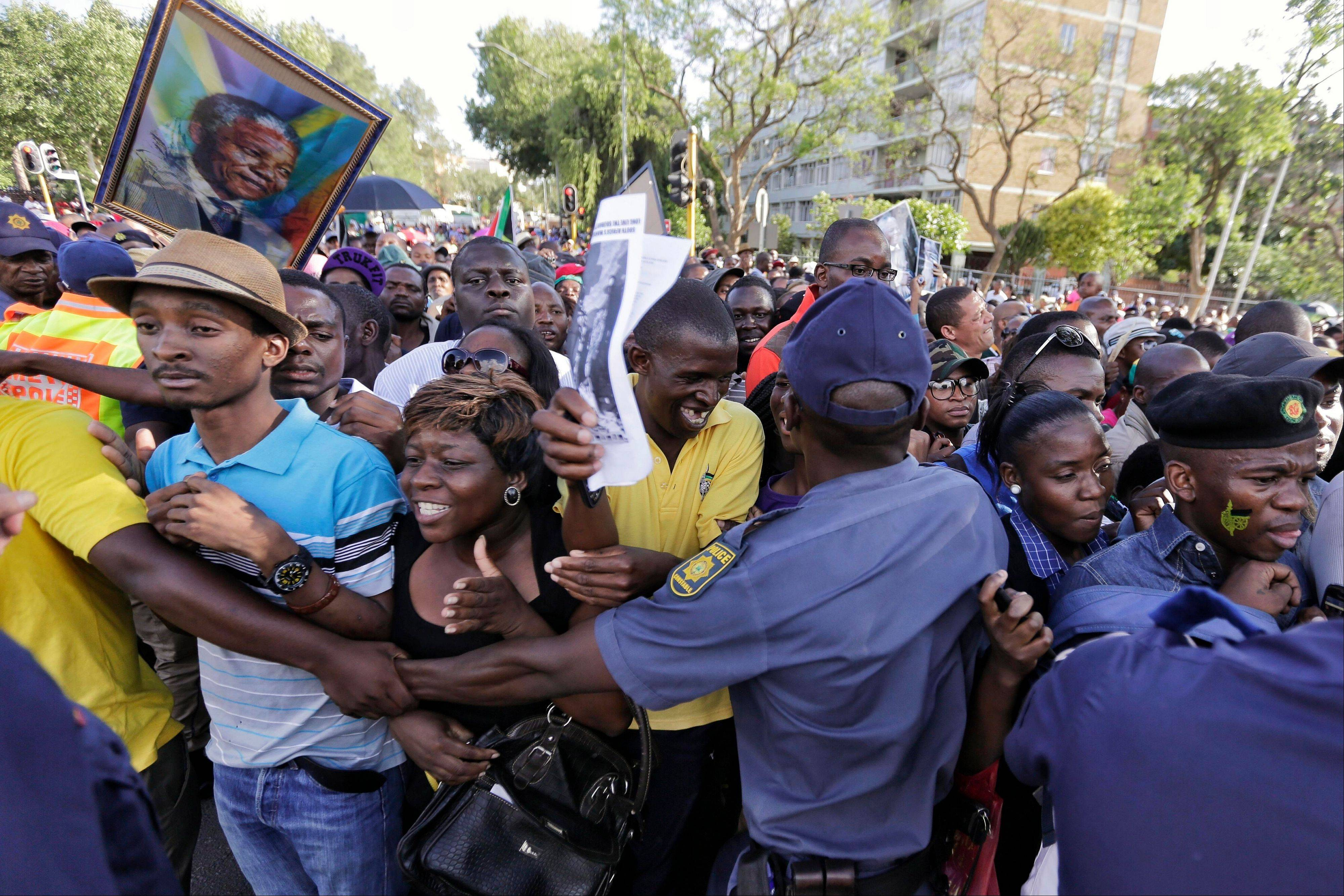 Police officers try to control the crowd after they announced they would reopen the entrance to the Union Buildings to pay their respects to Nelson Mandela, in Pretoria, South Africa, Friday, Dec. 13, 2013. Former South African President Nelson Mandela is on the third and final day of lying in state at the Union Buildings in Pretoria.