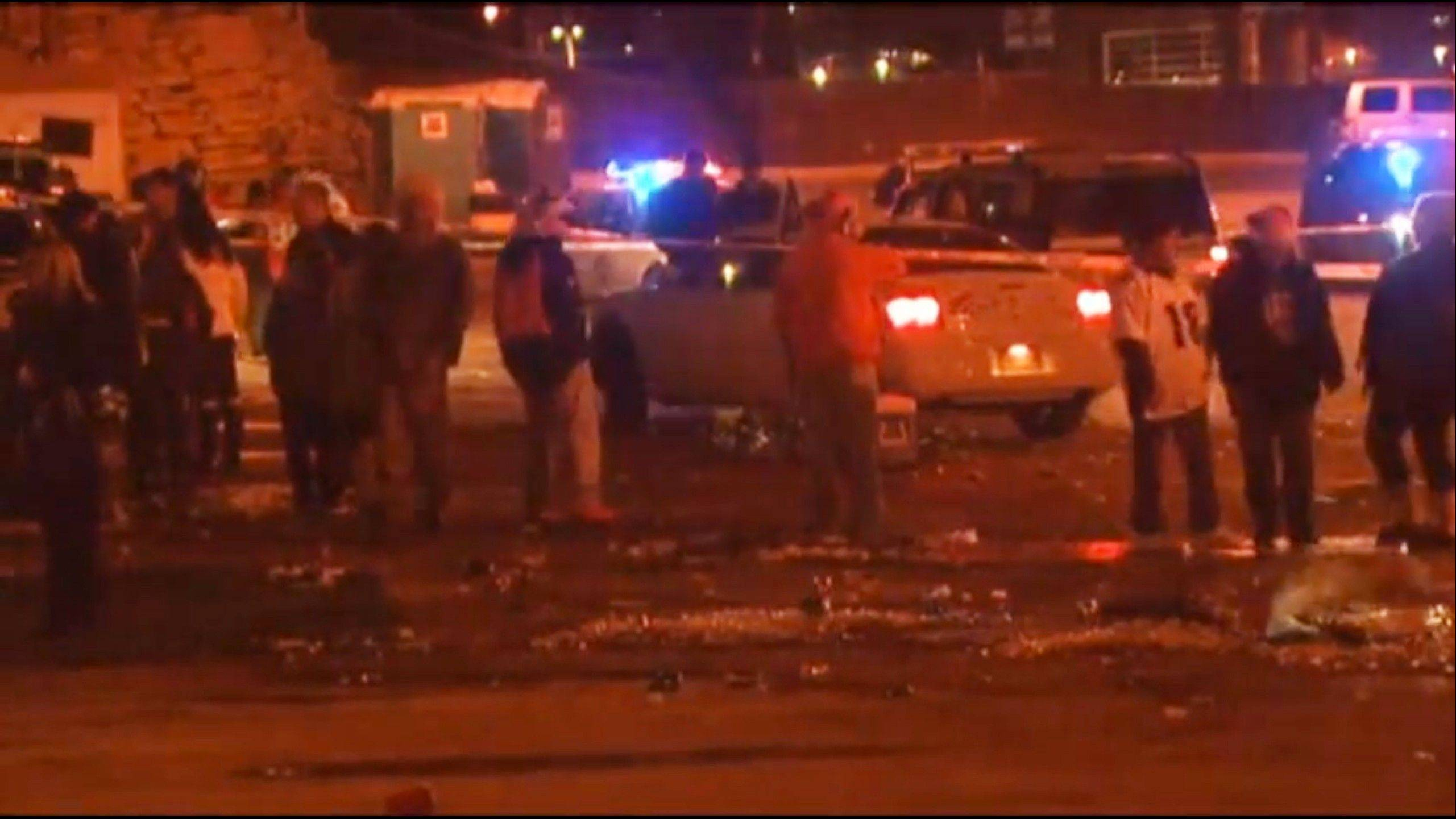 People mill around the area where at least three people were stabbed Thursday night Dec. 12, 2013, in a parking area at Sports Authority Stadium Field at Mile High after the Denver Broncos� game.