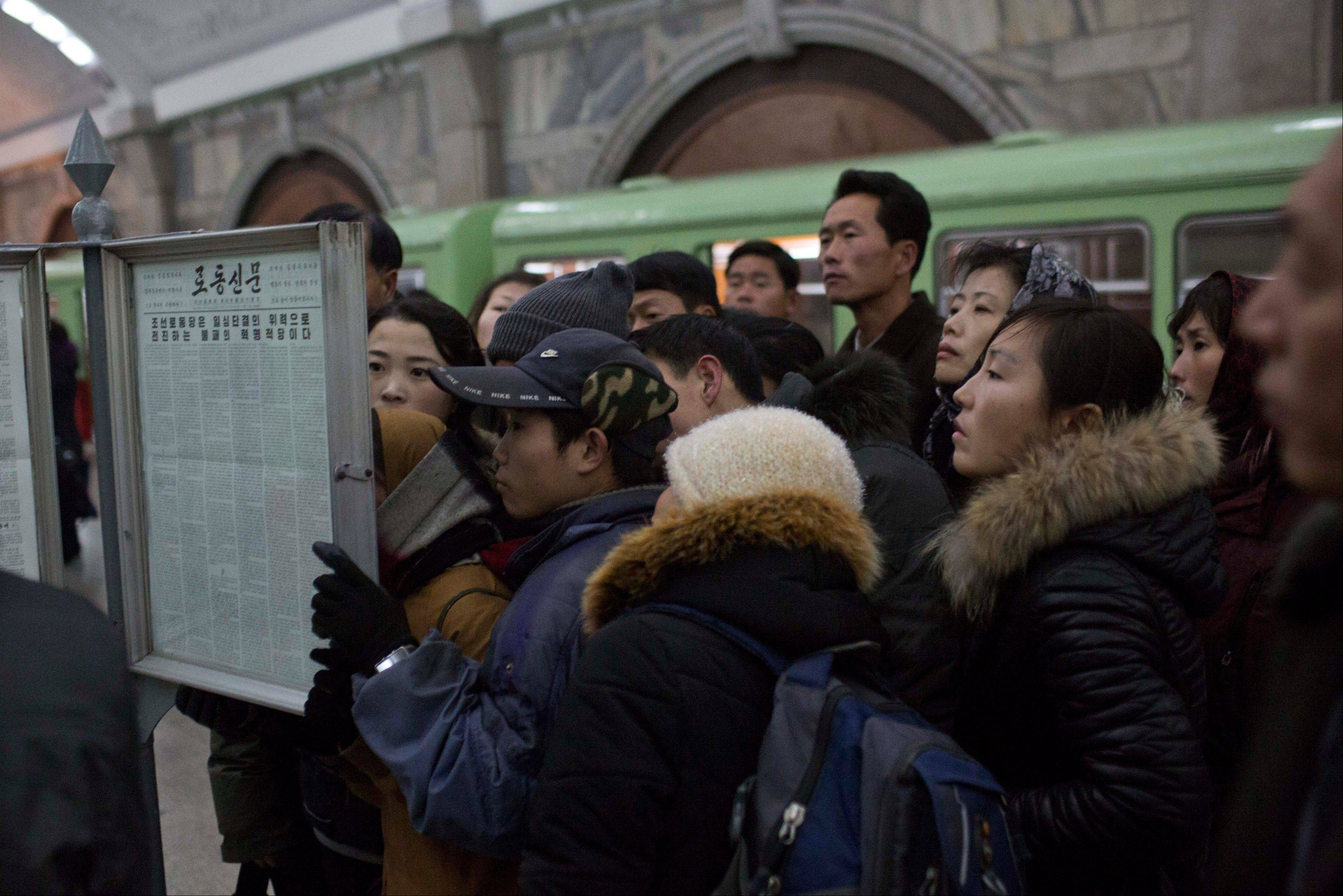North Korean subway commuters gather around a public newspaper stand on the train platform in Pyongyang, North Korea on Friday, Dec. 13, 2013, to read the headlines about Jang Song Thaek, North Korean leader Kim Jong Un�s uncle who was executed as a traitor.