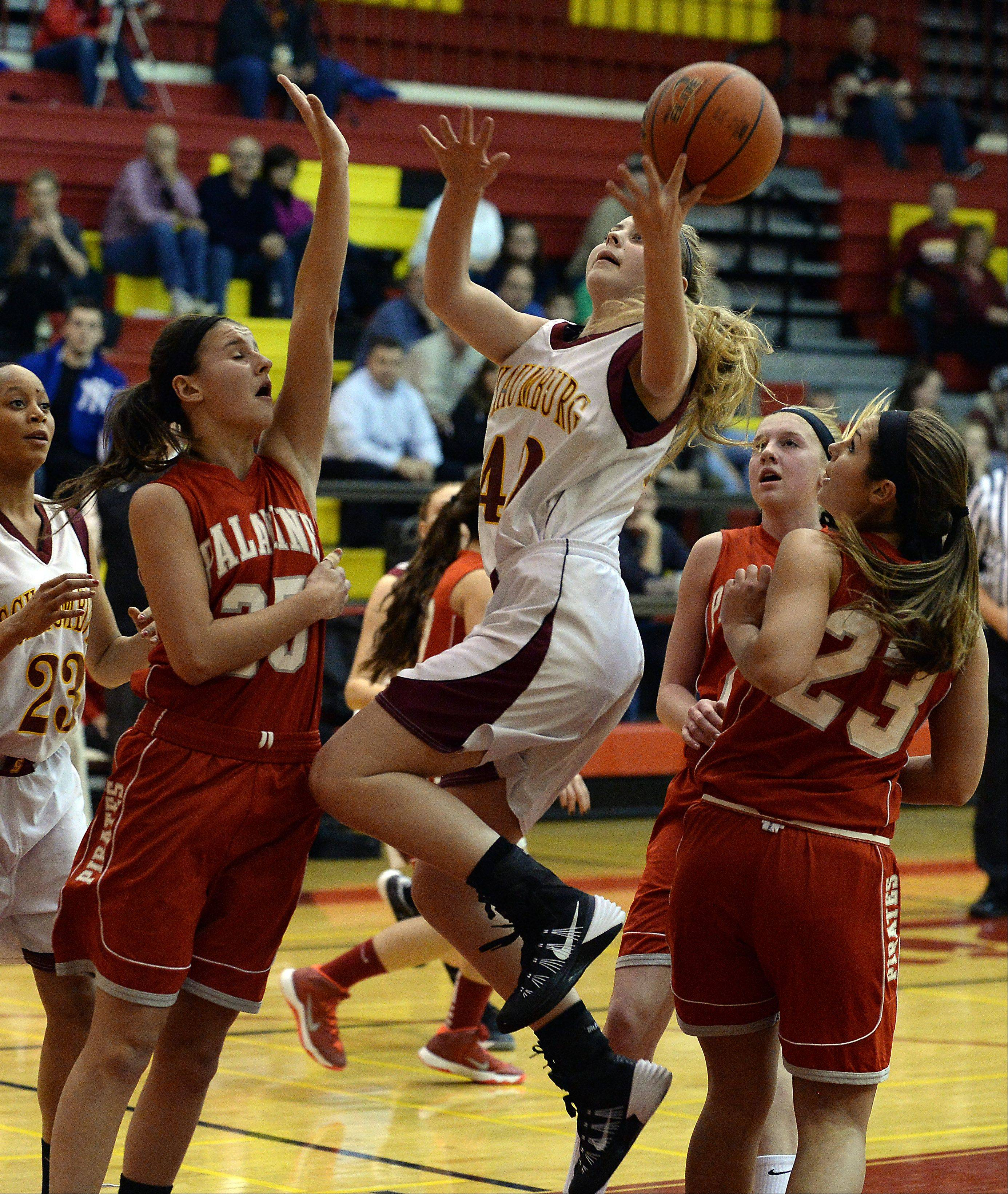 Schaumburg�s Mallory Gerber drives as Palatine�s Erin Mayer and Morgan Gallagher block her path in the first quarter of girls varsity basketball at Schaumburg on Friday.