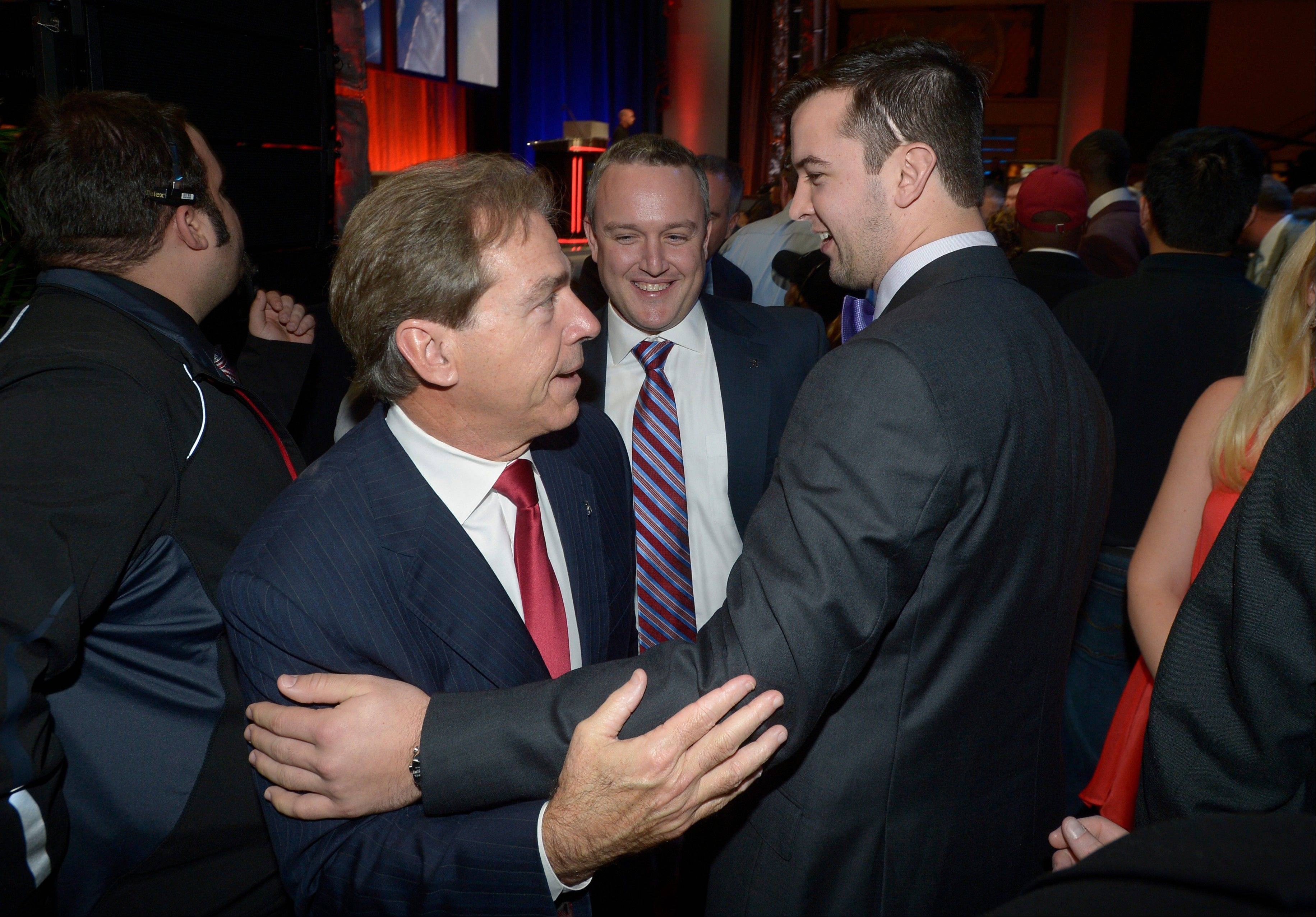 Alabama quarterback AJ McCarron, right, is congratulated by head coach Nick Saban, left, as Jeff Purinton, football media relations director, watches after McCarron won the Maxwell Award during the College Football Awards show in Lake Buena Vista, Fla., Thursday, Dec. 12, 2013. (AP Photo/Phelan M. Ebenhack)