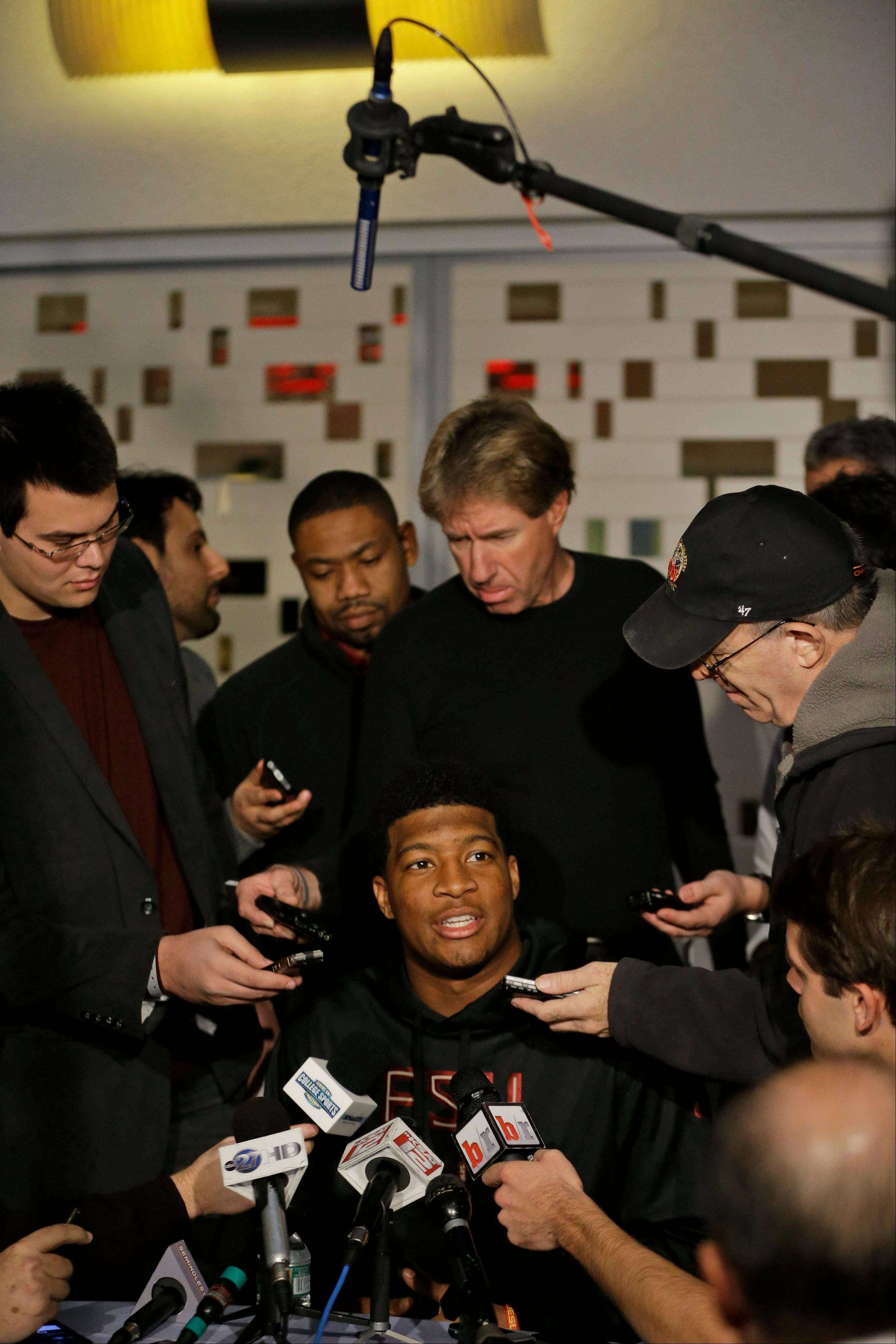Heisman Trophy finalist Jameis Winston, center, a quarterback at Florida State, talks to reporters during an informal media availability, Friday, Dec. 13, 2013, in New York. (AP Photo/Julio Cortez)