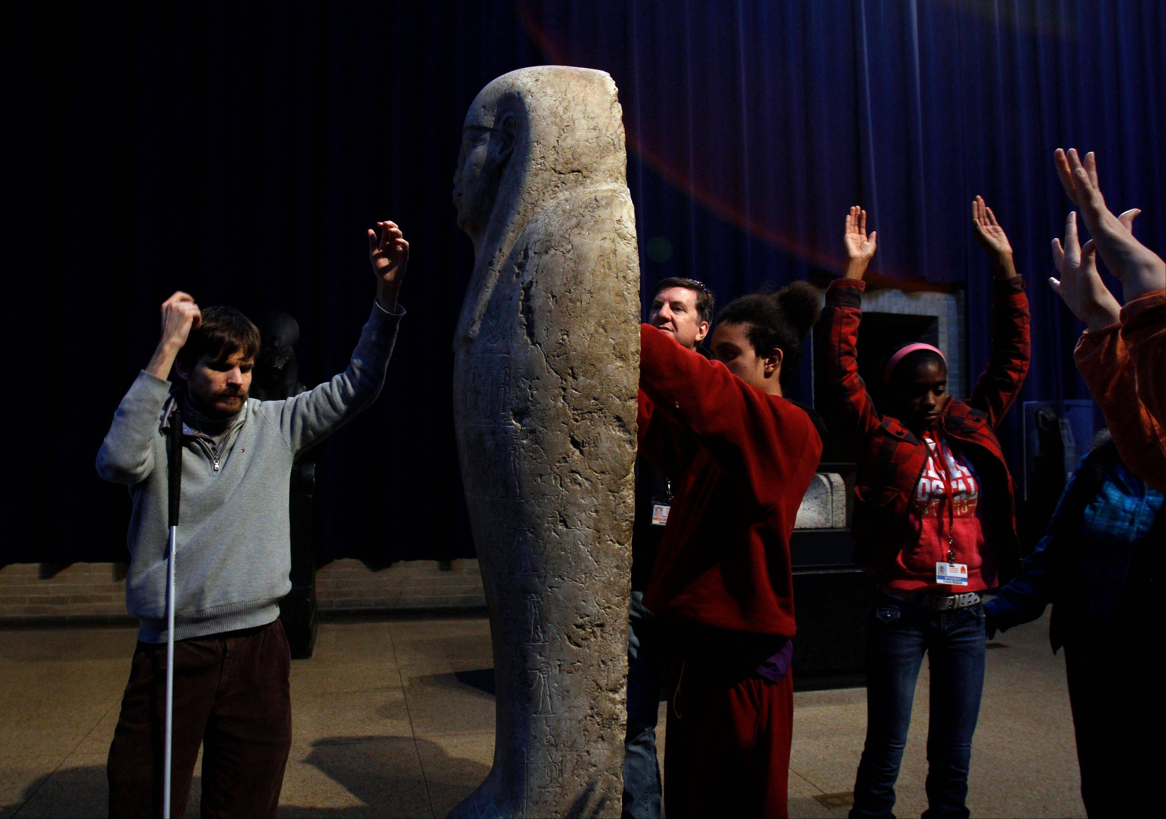 Docen Austin Seraphin, left, blind high school student Angel Ayala, center and blind high school student Cache Ballard, right, raise their arms as part of a lesson during a special tour for the blind and visually impaired at the Penn Museum in Philadelphia. The Penn Museum, part of the University of Pennsylvania, began offering touch tours to the blind and visually impaired in 2012 as part of an initiative to make their extensive collections more accessible. Seraphin is also blind and helped develop the tour.