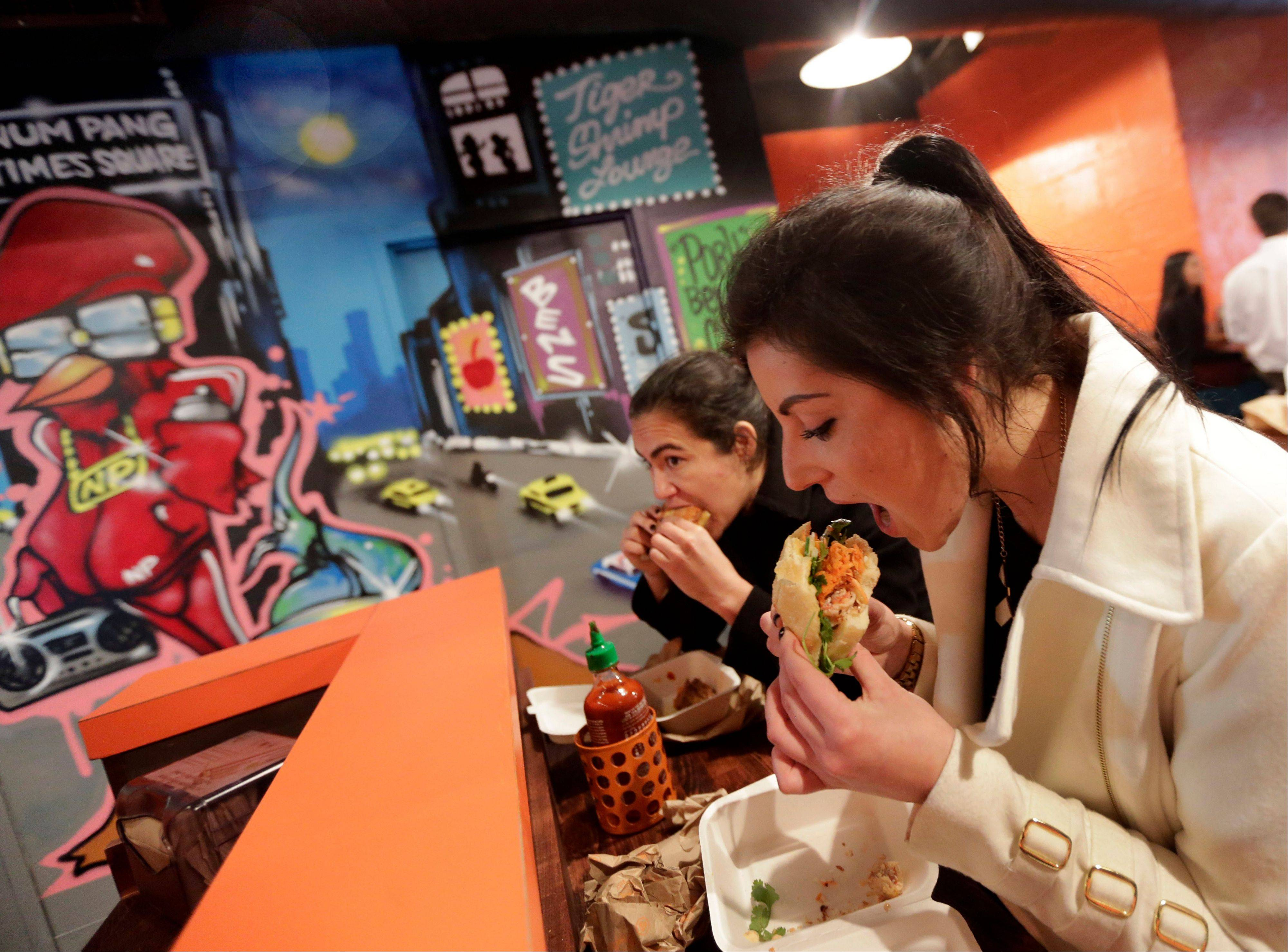Krista Agatielli, right, eats at Cambodian sandwich shop Num Pang, near New York's Rockefeller Center.