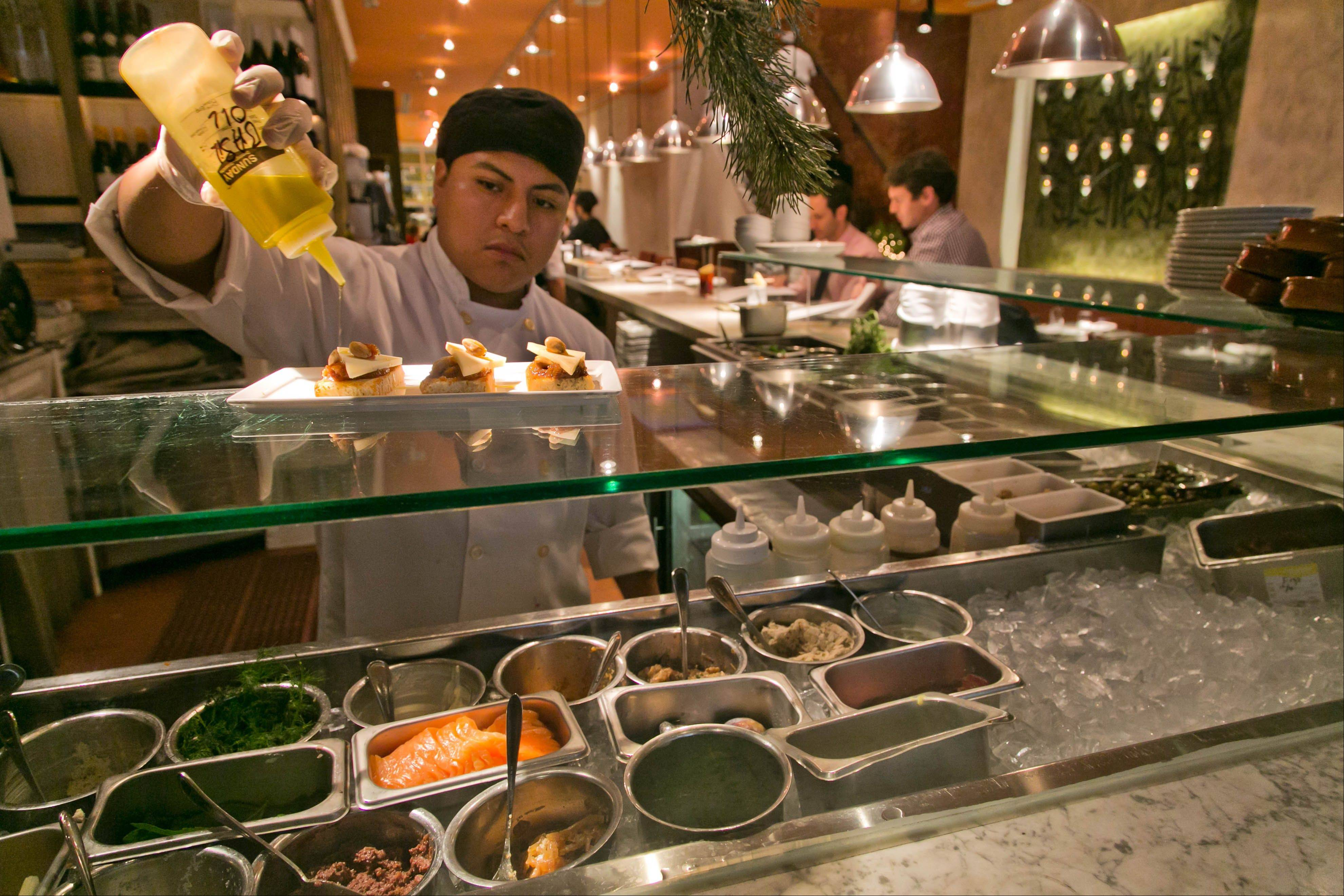 A dish gets prepped at Fig & Olive restaurant near New York's Rockefeller Center. Rockefeller Center is crowded at Christmastime, but visitors can choose from a variety of places to eat in the area, from ethnic food and street carts to sit-down dining.