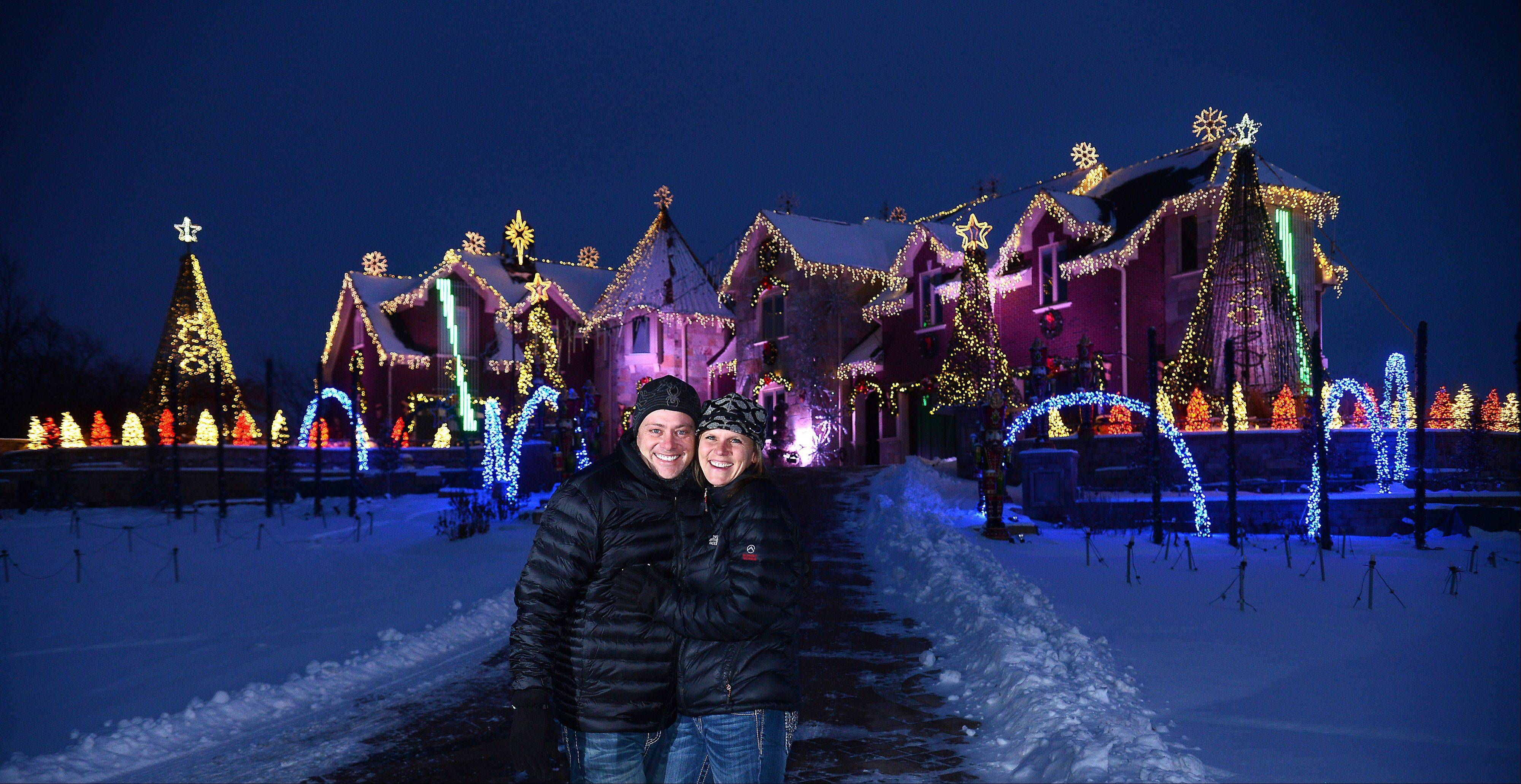 "Brian and Angela Larsen stand in front of their Elburn home, which is in the running for a $50,000 prize on ""The Great Christmas Light Fight,"" which airs at 8 p.m. Monday."