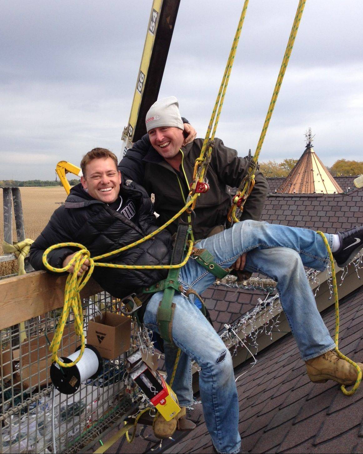 "Brian Larsen, left, and James Smith enjoy a moment while installing some 1 million lights on Larsen's Elburn home. Larsen's display is featured in an ABC reality TV series, ""The Great Christmas Light Fight,"" which airs at 8 p.m. Monday."
