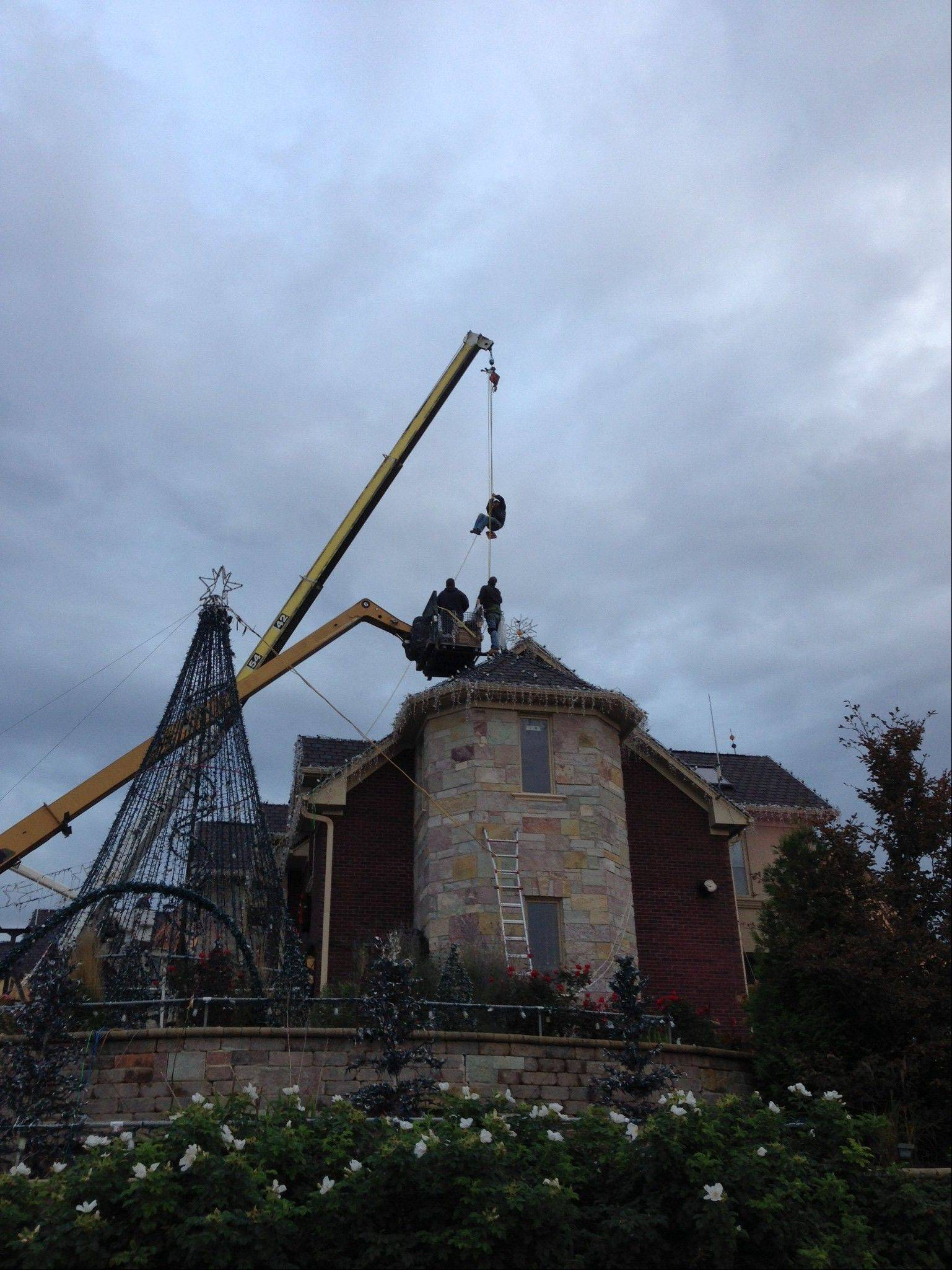 Crews utilized bucket trucks and a crane to install some 1 million lights in October on Brian Larsen's home in Elburn. The crane was used to lower men in harnesses onto the roof, so they could move freely without fear of falling.