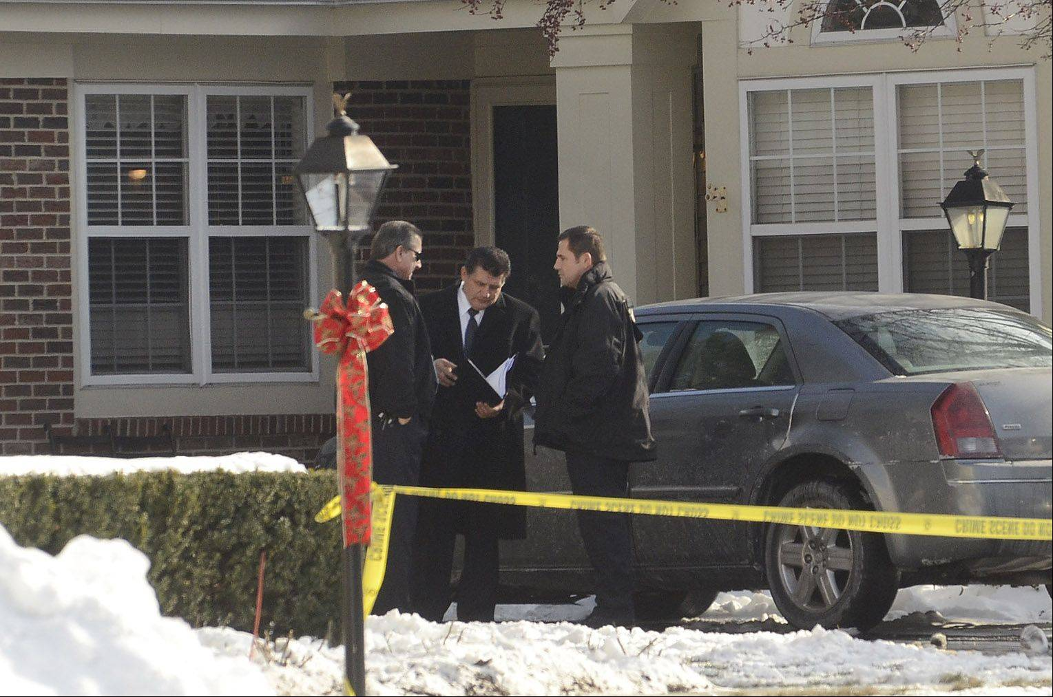 Police Friday continue to investigate the Thursday night shooting scene on the 1900 block of Windham Court, in the background, in Arlington Heights.