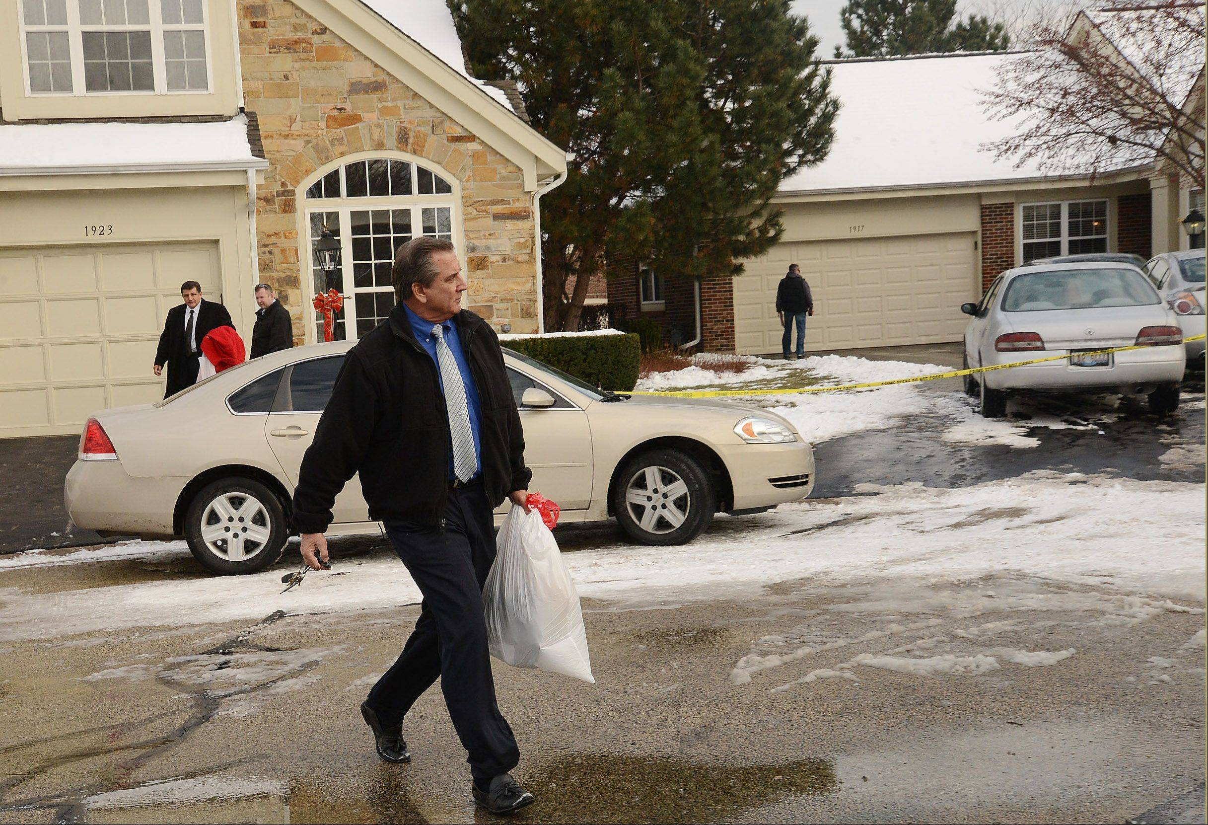 An investigator carries a bag taken Friday from the home on the 1900 block of Windham Court, right, as police continue to investigate the Thursday night shooting scene in Arlington Heights.
