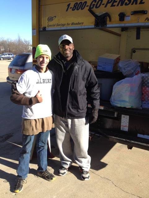 Midwest Sports Academy CEO/Founder Jim Cook poses with one of the volunteers who helped him unload the truck filled with donated supplies for victims of the tornadoes that struck Washington, Illinois, in November.