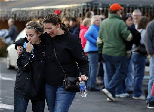 Parents stand along the tennis court fence hoping to see if their child is standing outside on the football field after a gunman was spotted inside Arapahoe High School on Friday, Dec. 13, 2013, in Centennial, Colo. Authorities said the gunman shot two students and then turned the gun on himself.