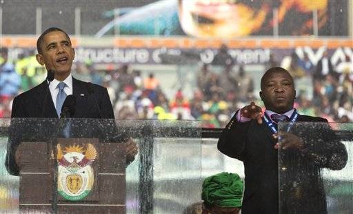 Thamsanqa Jantjie, right, interprets in sign language for President Barack Obama during his remarks at a memorial service at FNB Stadium in honor of Nelson Mandela in Soweto, near Johannesburg. The South African government says it is aware of reports that Jantjie faced a murder charge a decade ago, and says he is being investigated.