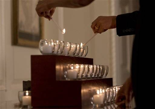 Twenty-six candles are lit by President Barack Obama and first lady Michelle Obama in honor of the Newtown shooting victims, in the Map Room of the White House in Washington, Saturday, Dec. 14, 2013, on the one year anniversary of the massacre.