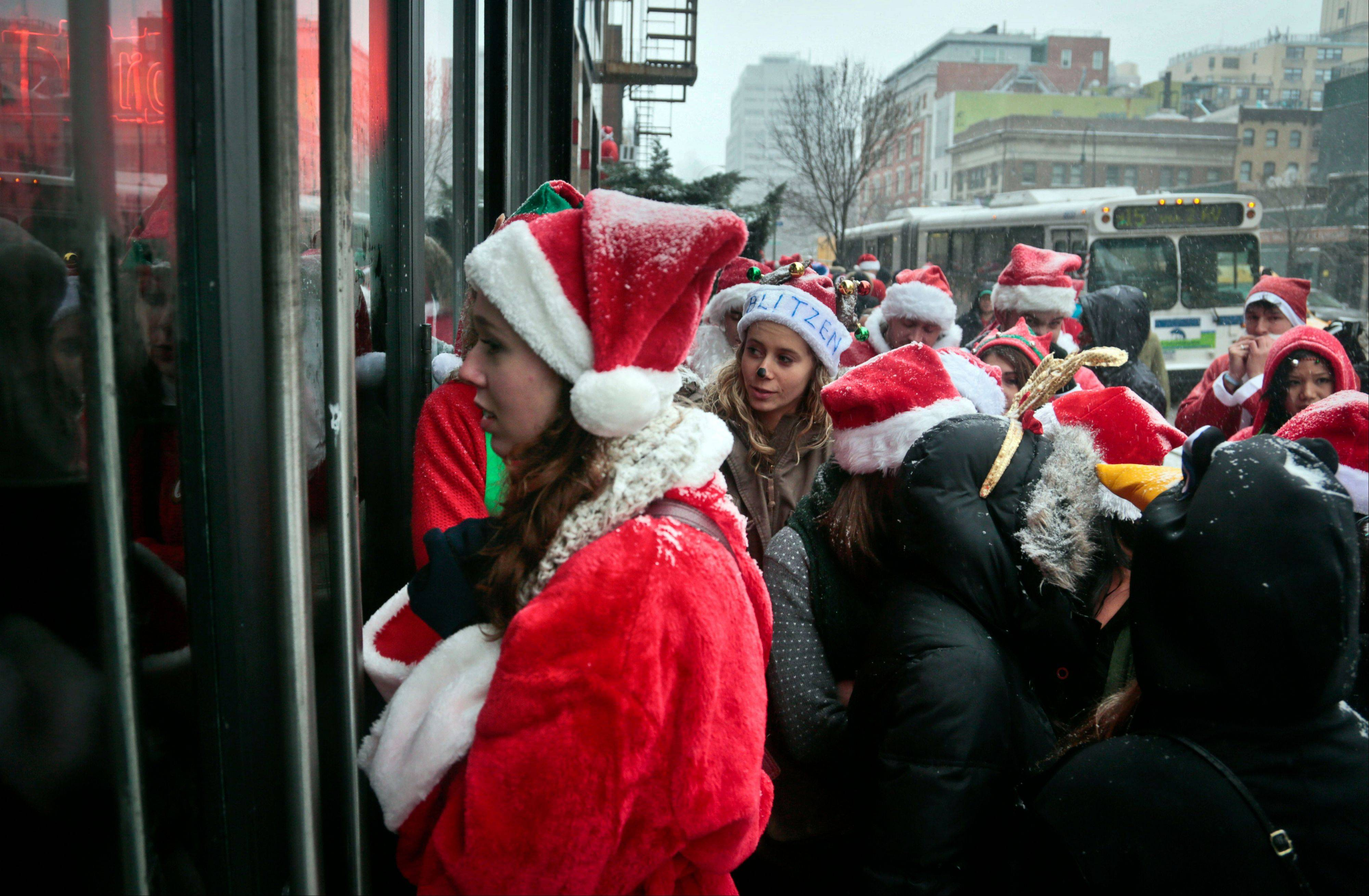 Santacon participants wait Saturday outside a lower eastside N.Y. bar filled to capacity. Thousands of red-suited revelers spread out through the city�s bars and snowy streets amid criticism that the event has become too rowdy.