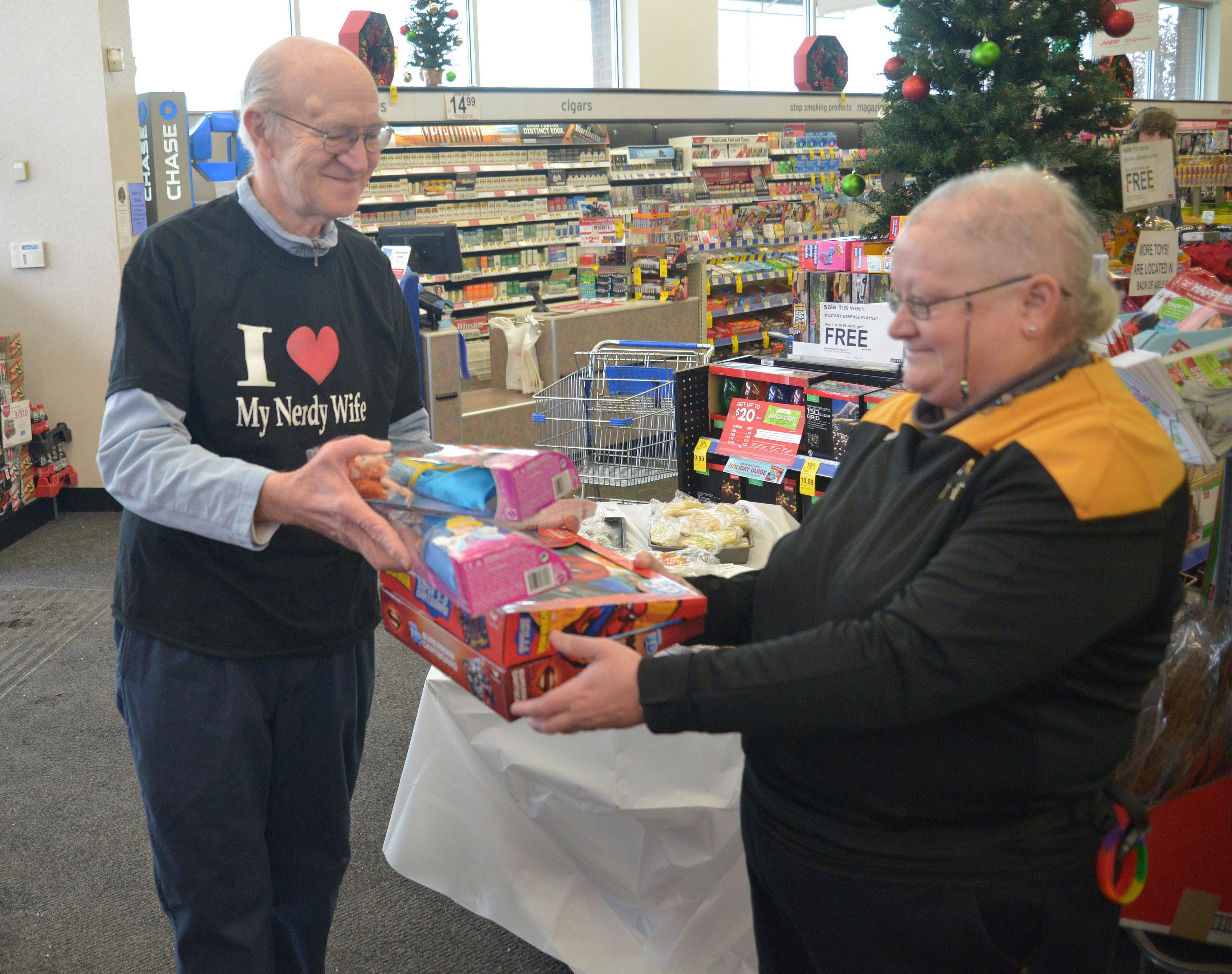 Richardson Knutson hands Elizabeth Rahuba gifts Saturday. Star Trek fans who are members of Klingon Assault Group, Klingon Armada International and the USS Chicago, held a Toys for Tots event from 10 a.m. to 2 p.m. at Walgreens in Naperville.