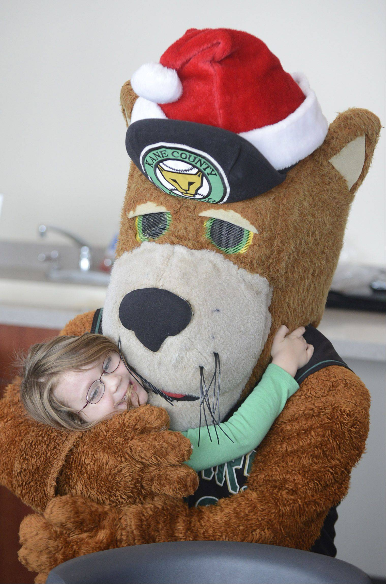 Abigail Bowgren, 5, of Geneva throws her arms around Ozzie the Cougar after decorating holiday cookies at the Kane County Cougars� second annual holiday event at Fifth Third Ballpark in Geneva Saturday.