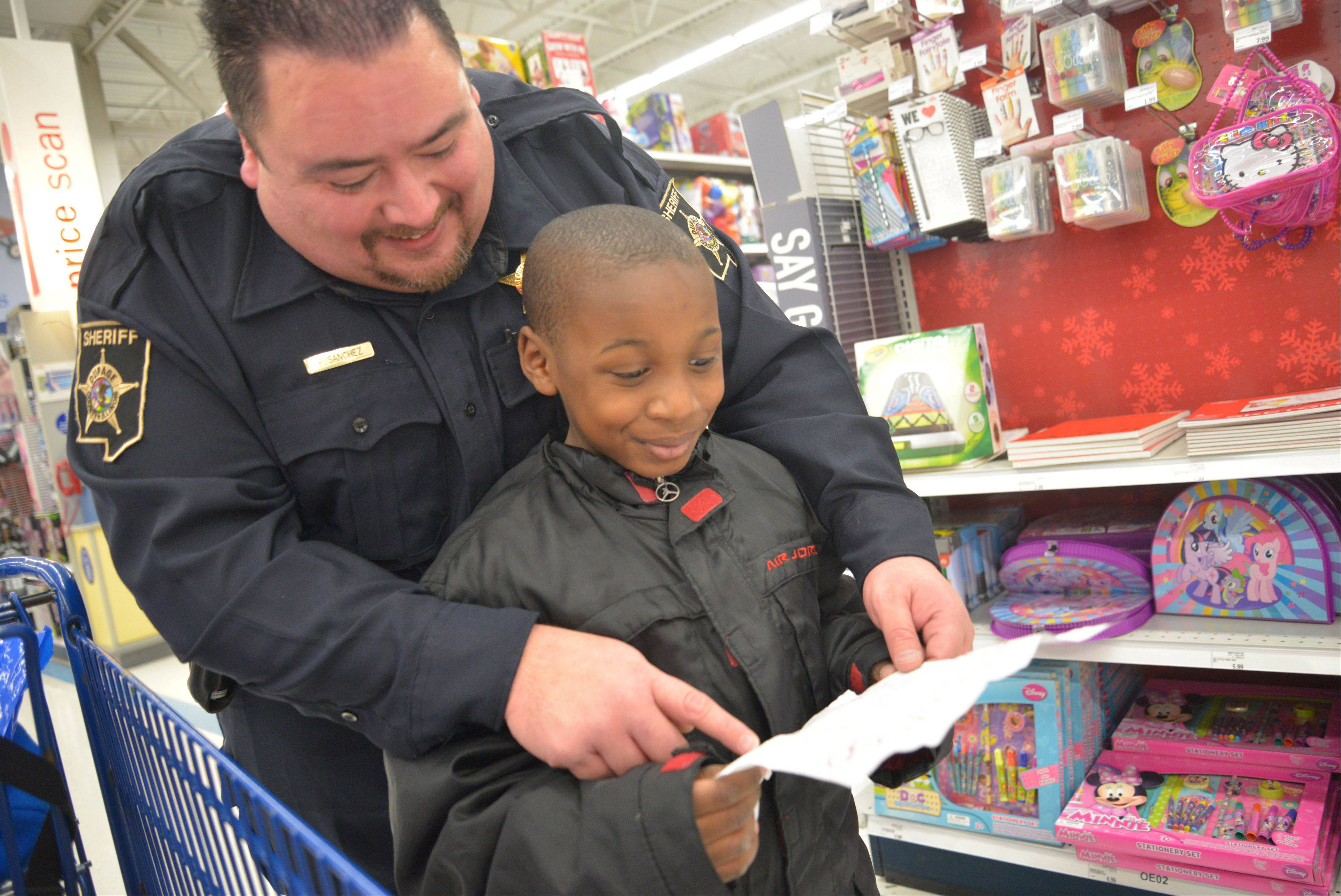 DuPage County sheriff�s Deputy Fernando Sanchez helps Kaleb Vaughn, 8, of Hanover Park check his shopping list Saturday at Meijer in Bloomingdale. DuPage�s sheriff�s office, an officers union, chiefs of police association and departments from at least nine towns combined to brighten the holidays for 70 children.