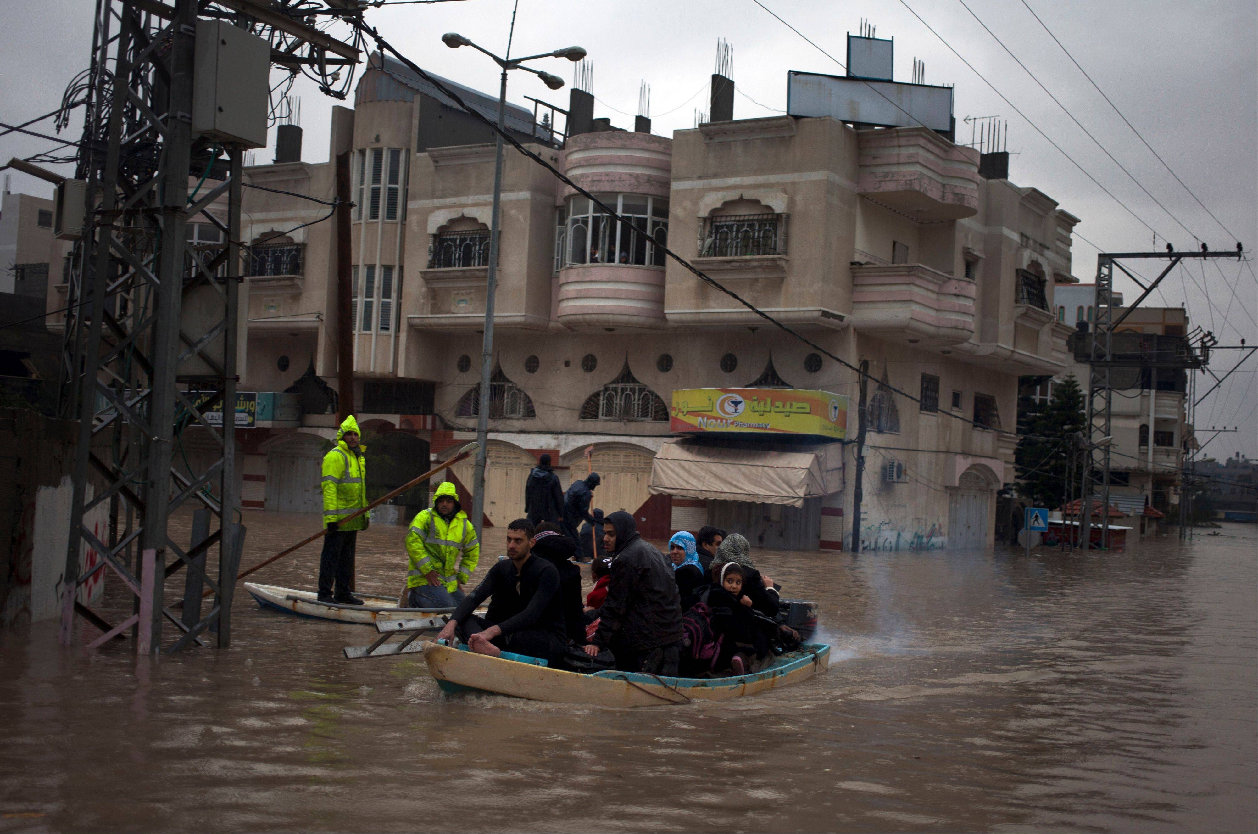 Palestinian rescue members evacuate residents Saturday using a fishing boat following heavy rains in Gaza City.