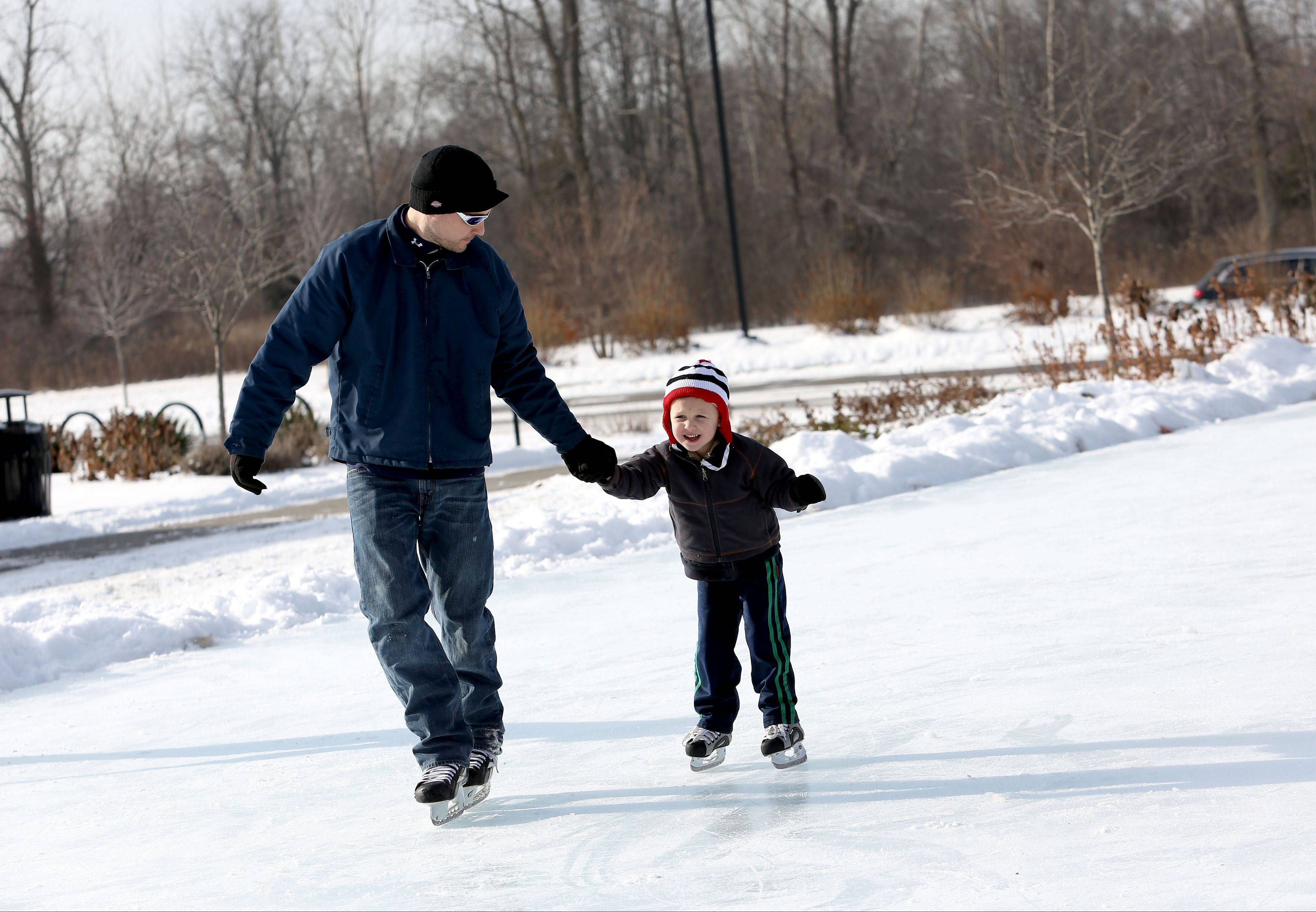 Eric Williamson of Naperville helps his son, Oslo, 4, around the outdoor ice skating rink Friday at the Nike Sports Complex in Naperville. With only one skater on the rink, there was plenty of room for the father and son to get comfortable on the ice. �We�re taking advantage of no people,� Williamson said.
