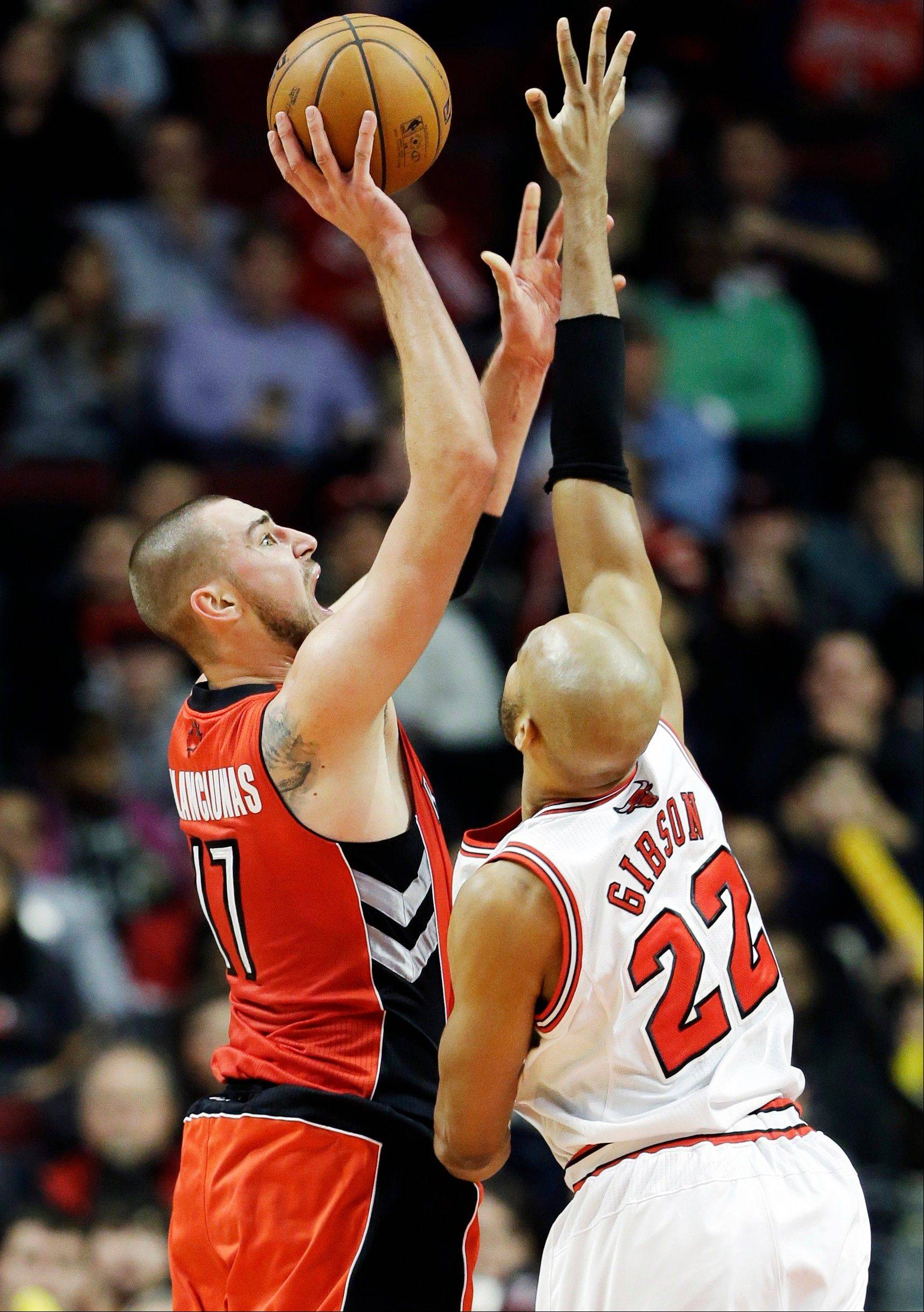 Toronto Raptors center Jonas Valanciunas, left, of Lithuania, shoots over Chicago Bulls forward Taj Gibson during the second half of an NBA basketball game in Chicago on Saturday. The Raptors won 99-77.