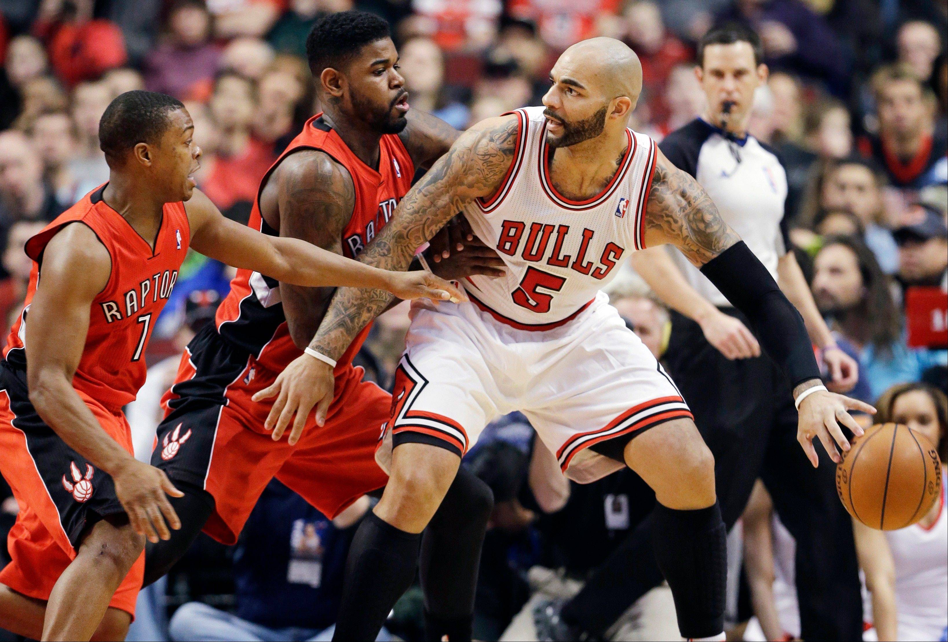 Bulls forward Carlos Boozer, right, controls the ball as Toronto Raptors forward Amir Johnson, center, and guard Kyle Lowry guard Saturday night at the United Center.