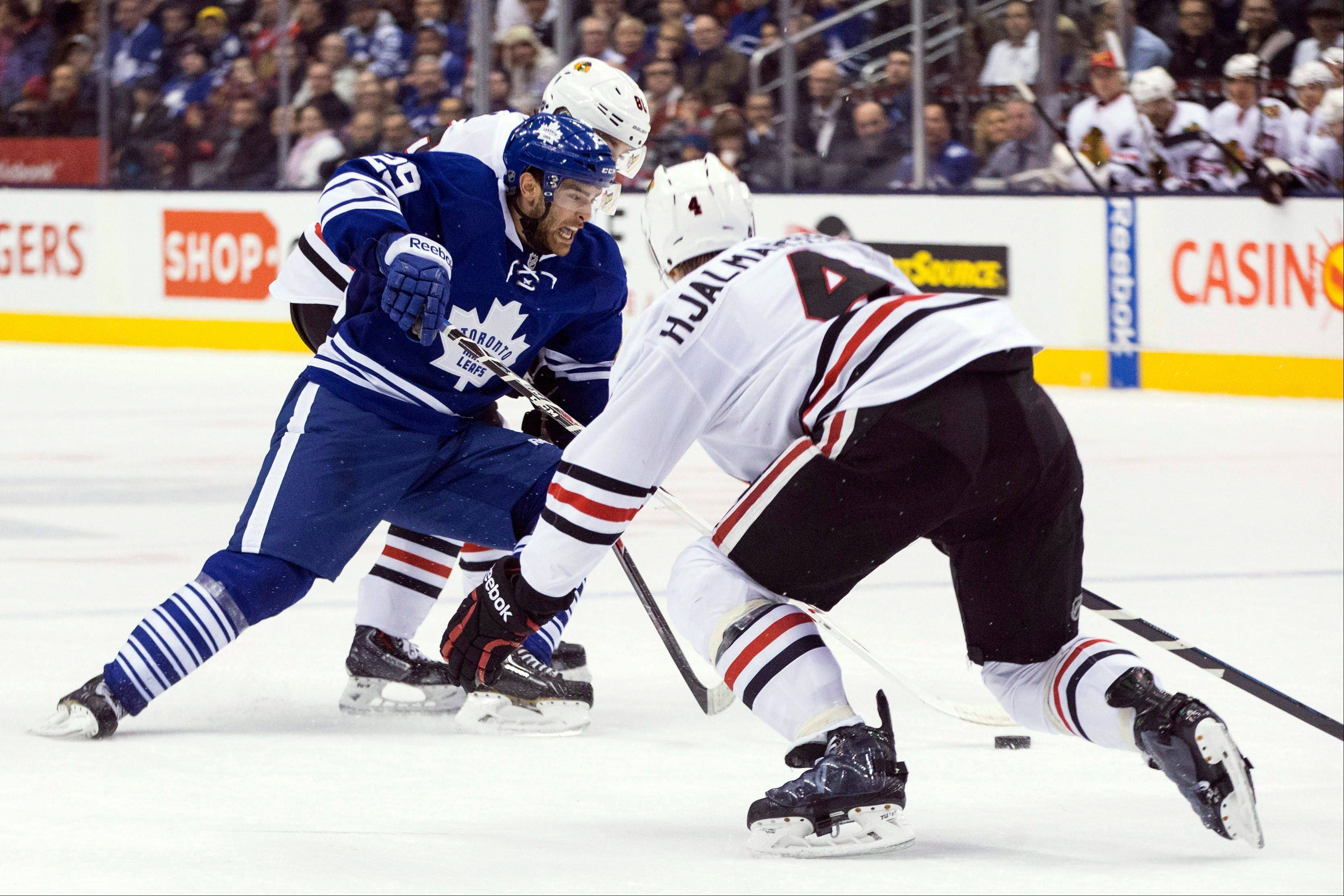 Toronto Maple Leafs� Jerry D�Amigo, left, battles for the puck with Chicago Blackhawks� Marian Hossa, back, as Niklas Hjalmarsson covers Saturday in Toronto. The Maple Leafs won 7-3.