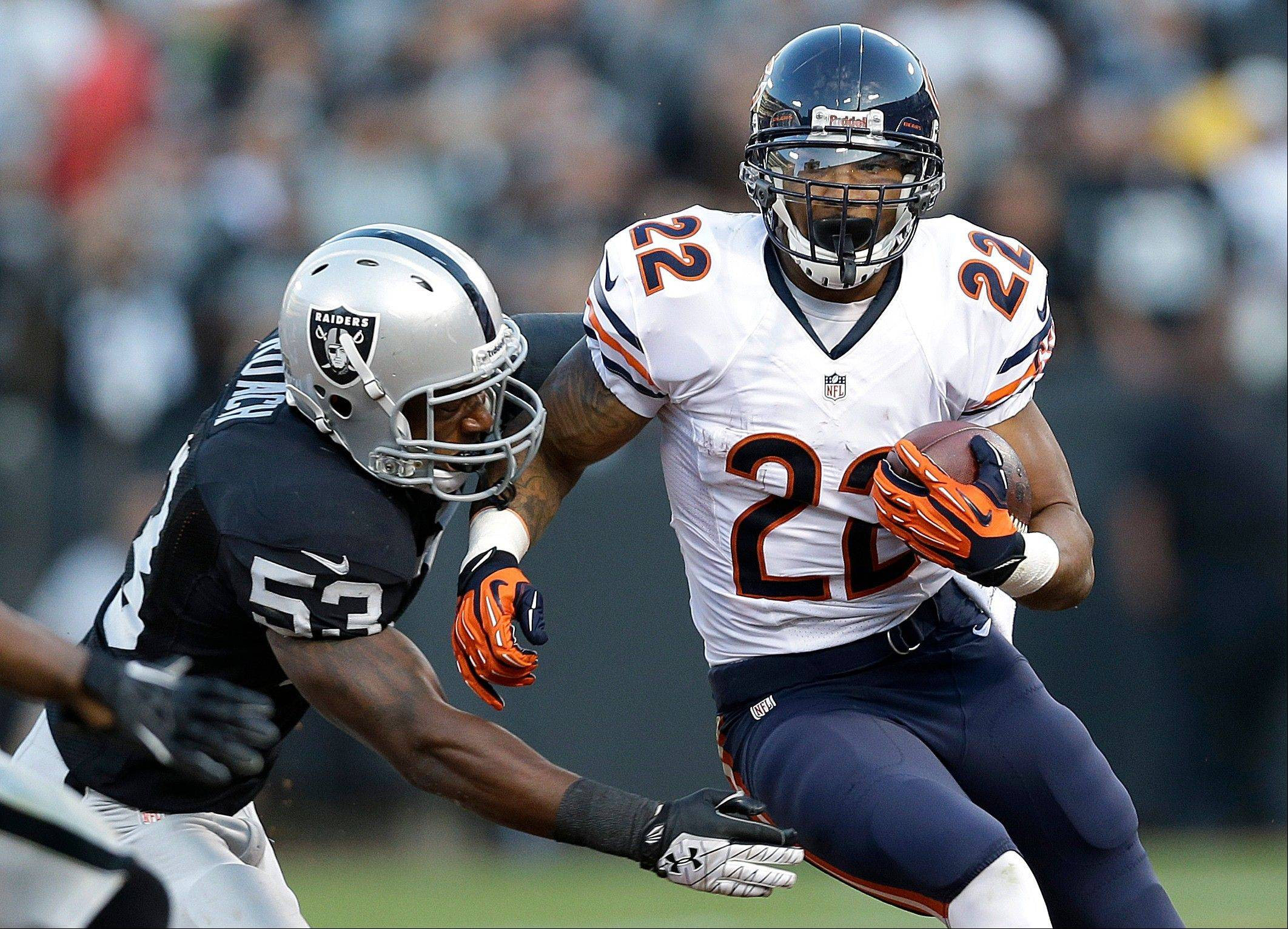 back Matt Forte carries against Oakland linebacker Nick Roach during a preseason game. Roach is having a solid season as the Raiders� middle linebacker.