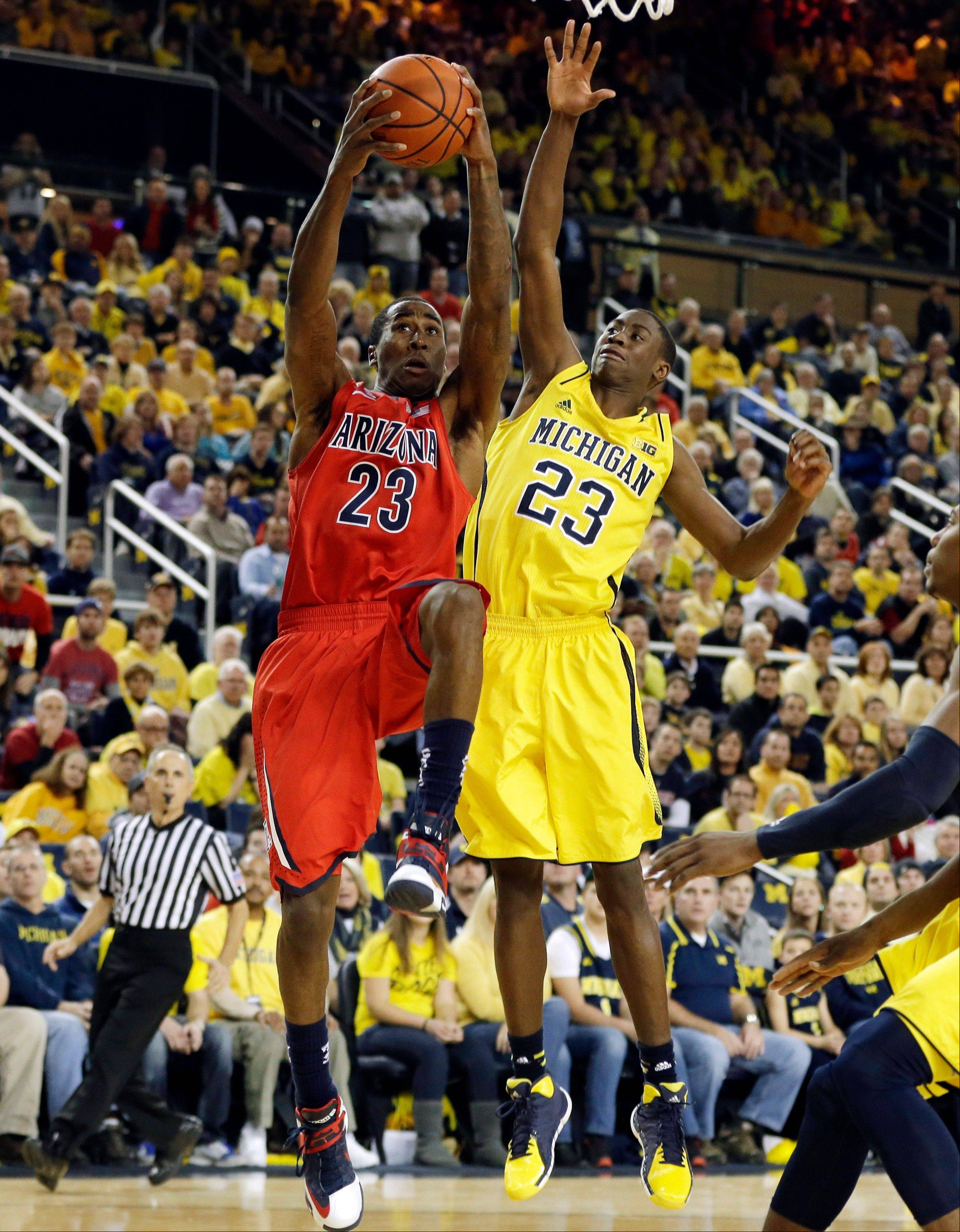 Arizona forward Rondae Hollis-Jefferson (23) is defended by Michigan guard Caris LeVert (23) during the second half of an NCAA college basketball game in Ann Arbor, Mich., Saturday, Dec. 14, 2013. (AP Photo/Carlos Osorio)