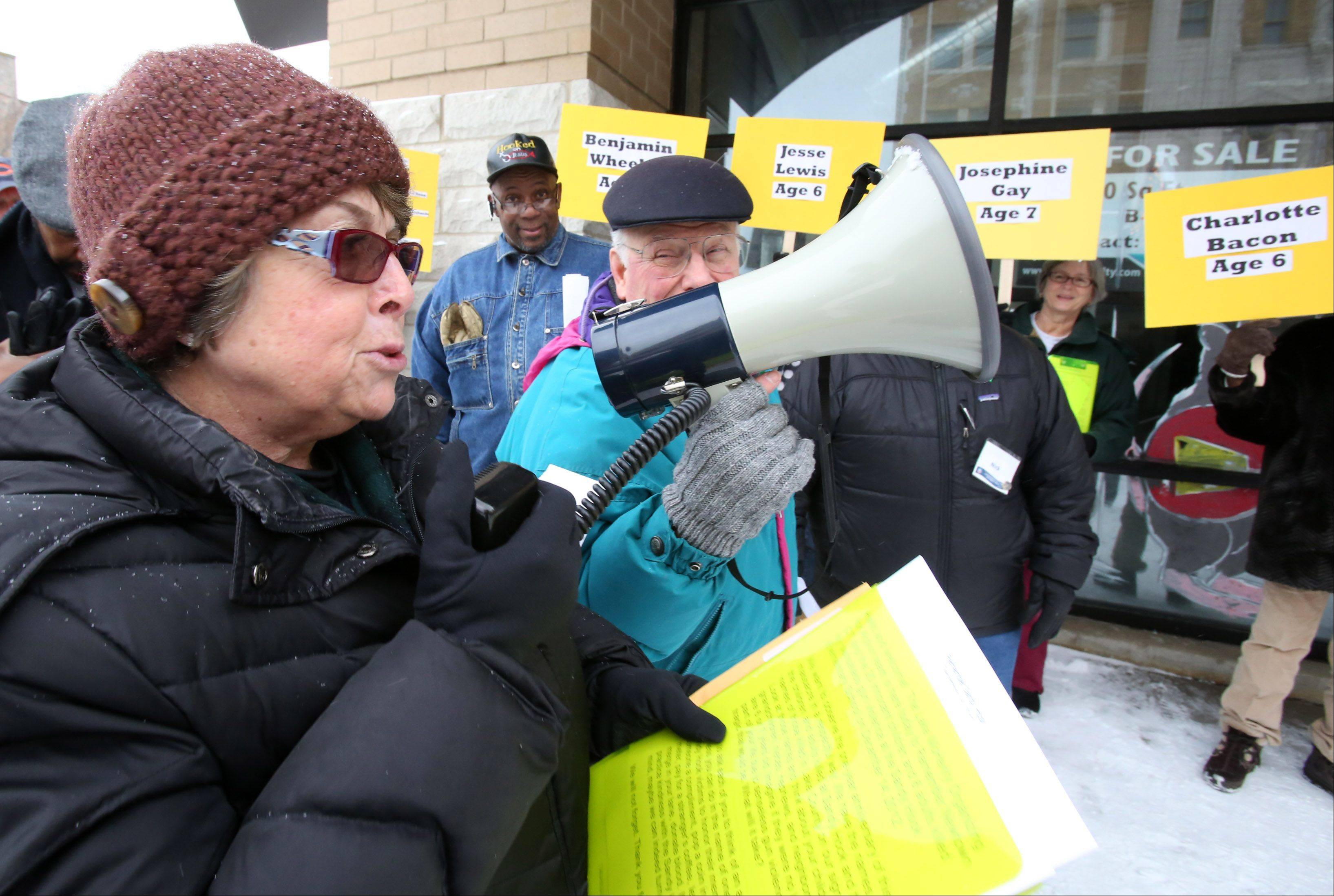 Fran Puchli, team leader with the Lake McHenry Chapter of Organizing for Action, asks people passing by to perform an act of kindness in remembrance of a school shooting that occurred Dec. 14, 2012, in Newtown, Conn. The Lake McHenry Chapter of Organizing for Action hosted a remembrance event Saturday in Waukegan.