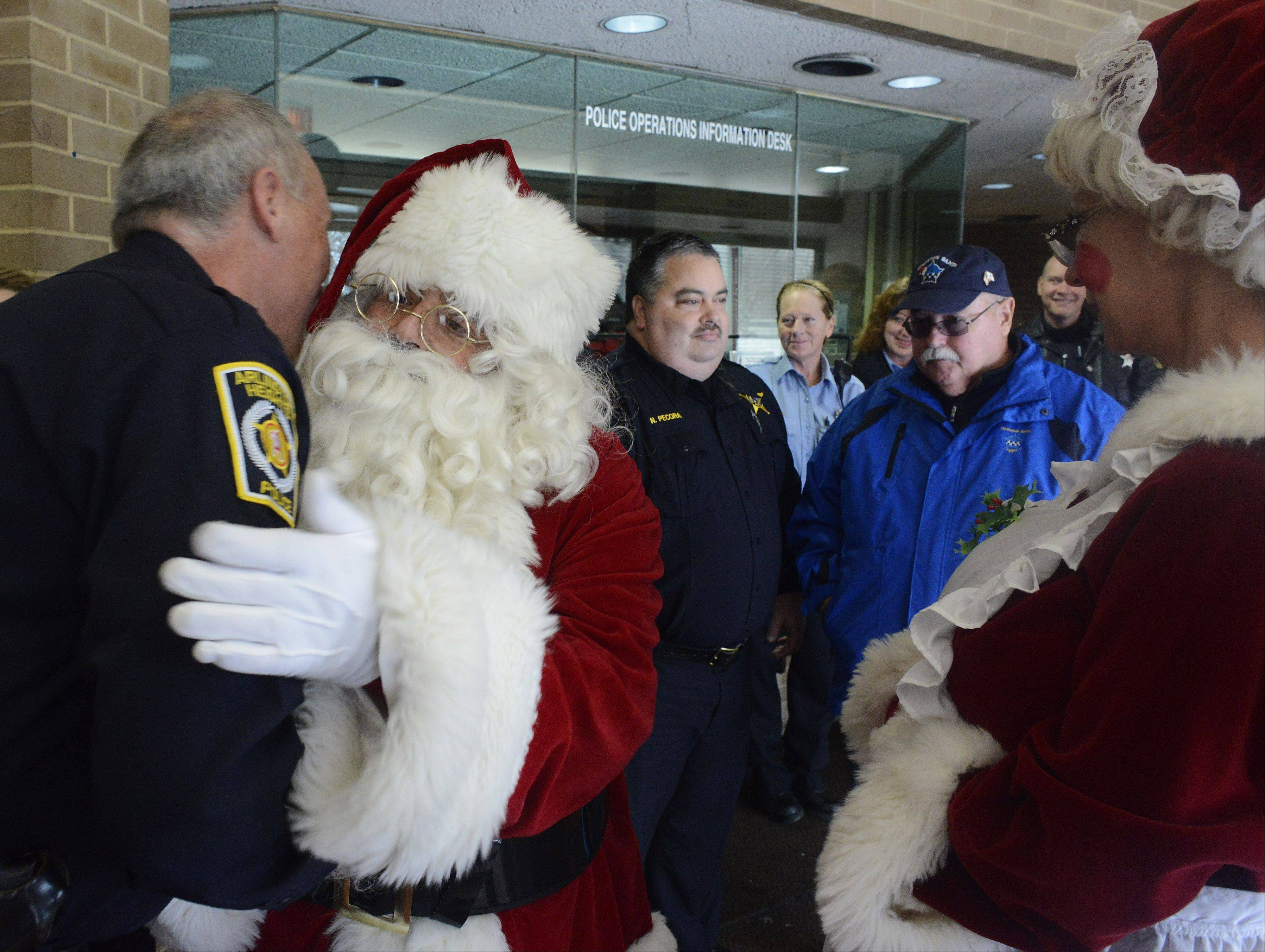 Arlington Heights Cmdr. Andrew Whowell gets a hug from Santa on Saturday as the Chicago Police Memorial Foundation's Operation Santa stops at the Arlington Heights Police Department to drop off gifts for Officer Michael McEvoy, who was shot Thursday in the line of duty.
