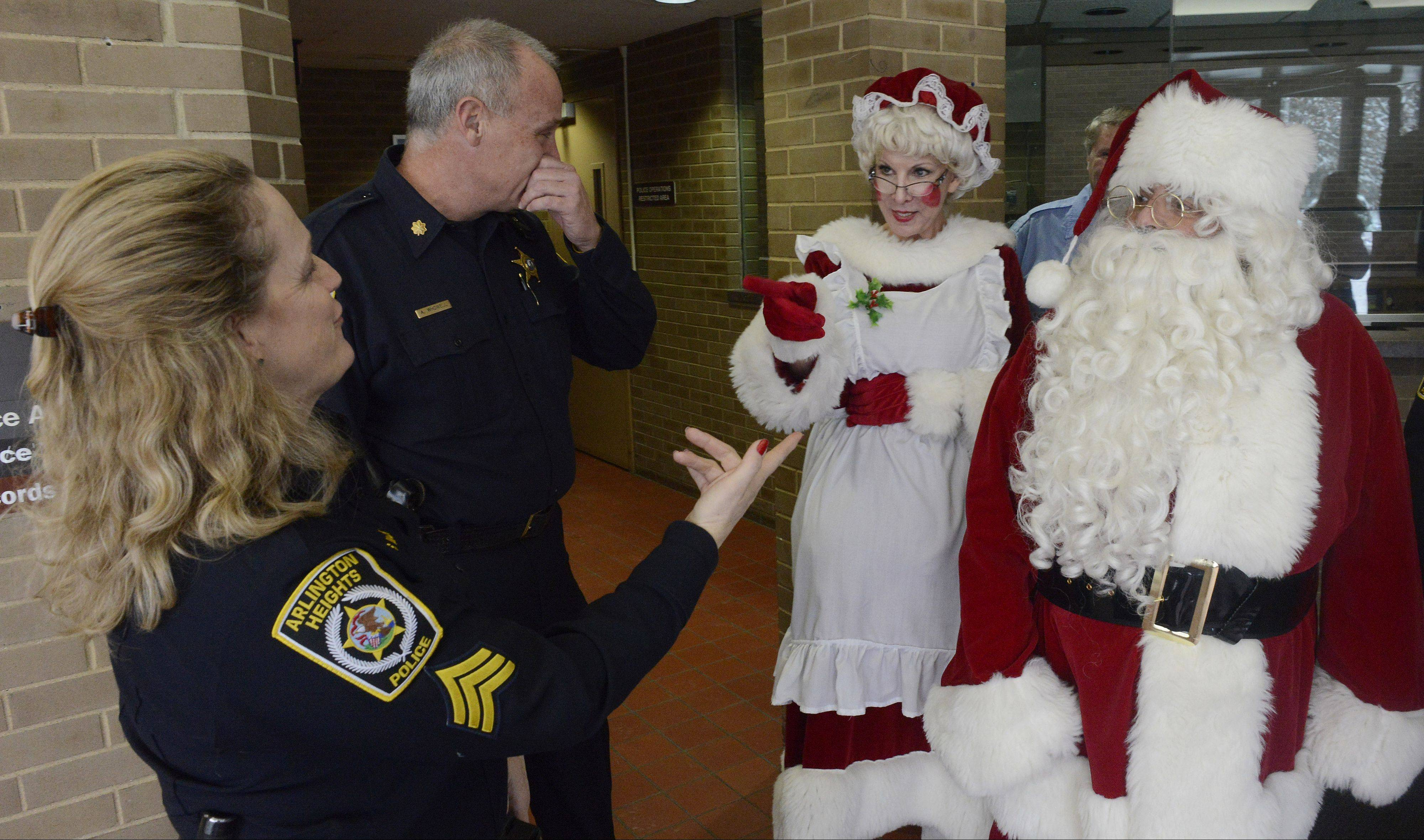 Sgt. Stephanie Mack, left, and Cmdr. Andrew Whowell say goodbye to Santa and Mrs. Claus at the conclusion of a stop Saturday by the Chicago Police Memorial Foundation's Operation Santa at the Arlington Heights Police Department to drop off gifts for Officer Michael McEvoy.