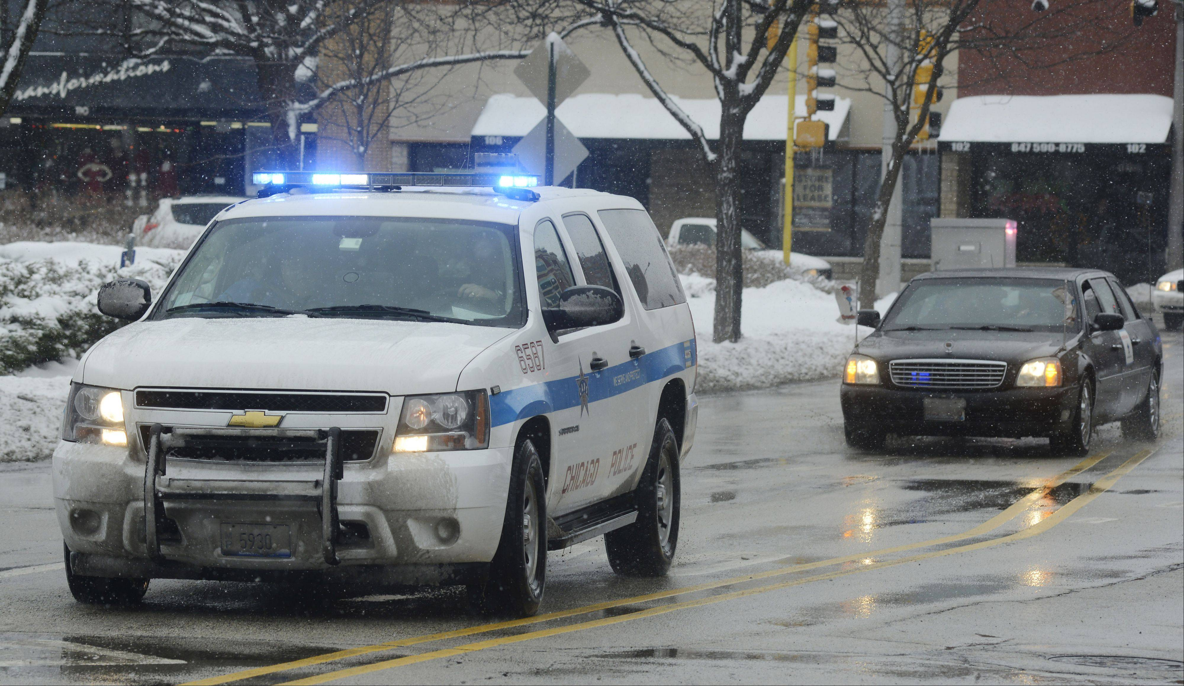 Vehicles from the Chicago Police Memorial Foundation's Operation Santa arrive at the Arlington Heights Police Department on Saturday to drop off gifts for Officer Michael McEvoy, who was shot in the line of duty on Thursday.