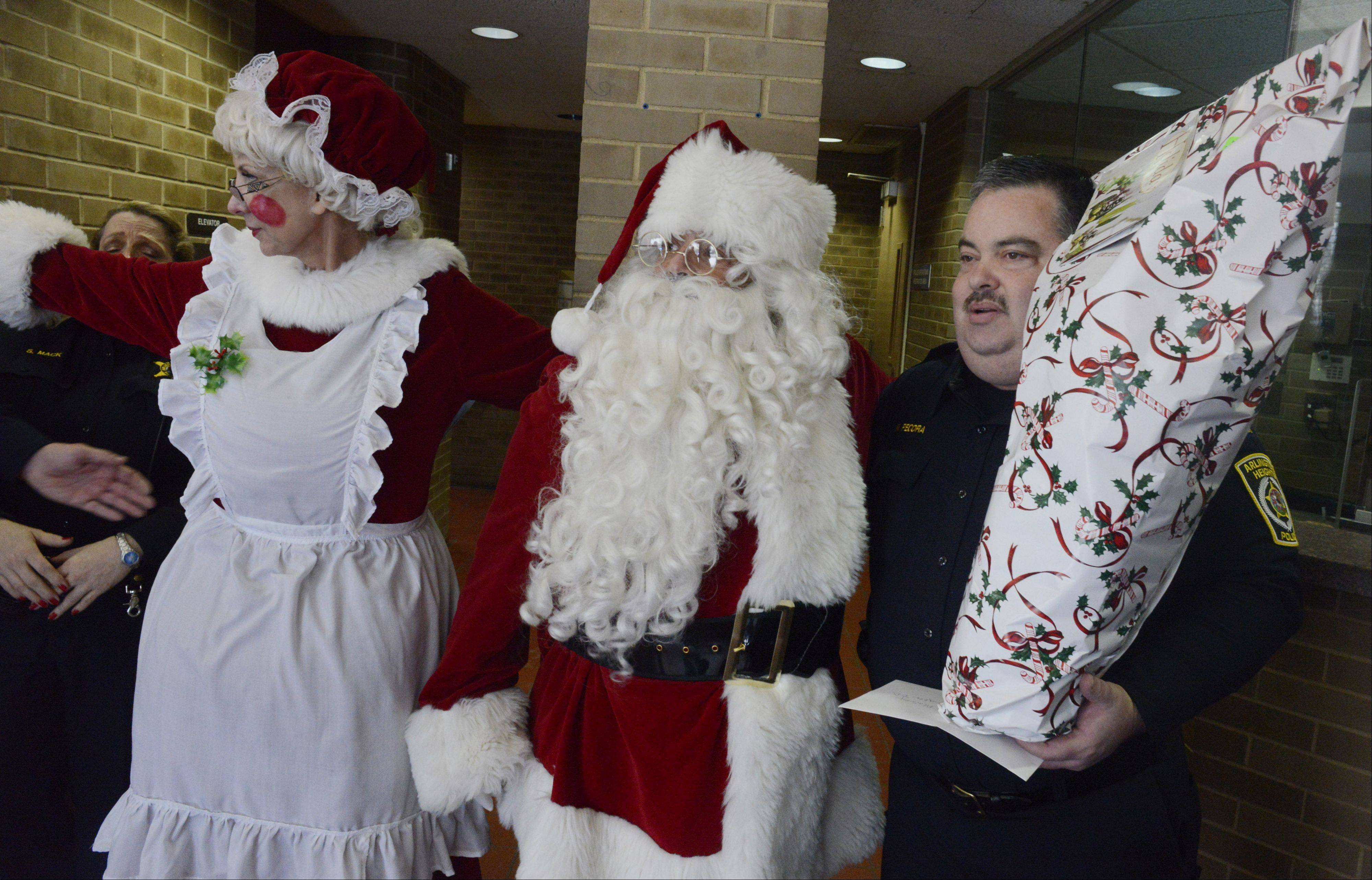 Arlington Heights Capt. Nick Pecora holds gifts for Officer Michael McEvoy, who was shot in the line of duty last week, as the Chicago Police Memorial Foundation's Operation Santa stops at the Arlington Heights Police Department on Saturday.