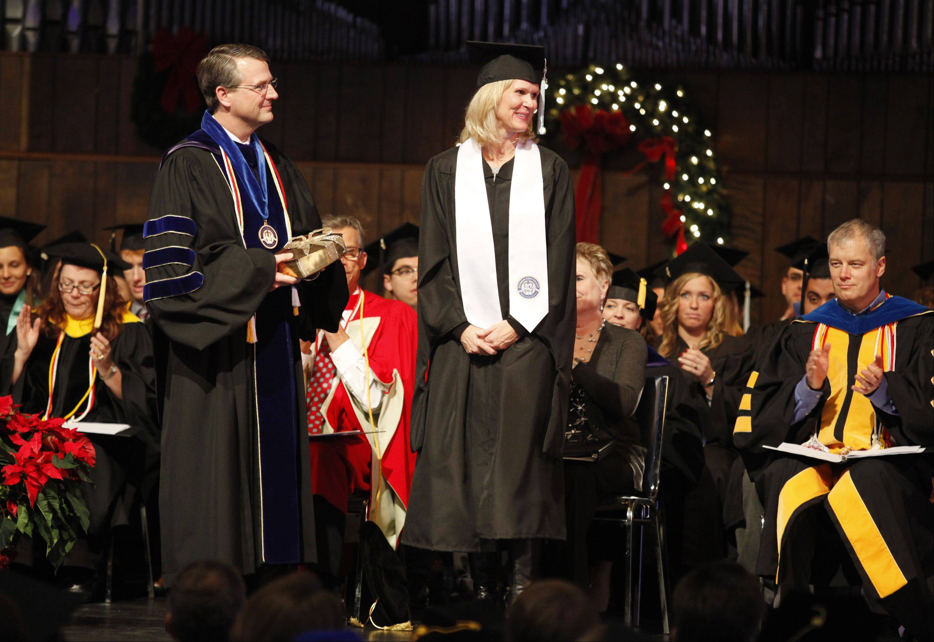 Judson University President Gene Crume, left, listens as accolades are read for Road to Damascus Award winner Kirsten Andler of Cary during a commencement ceremony Saturday at Judson University in Elgin. Andler received her Master of Education in Literacy degree.