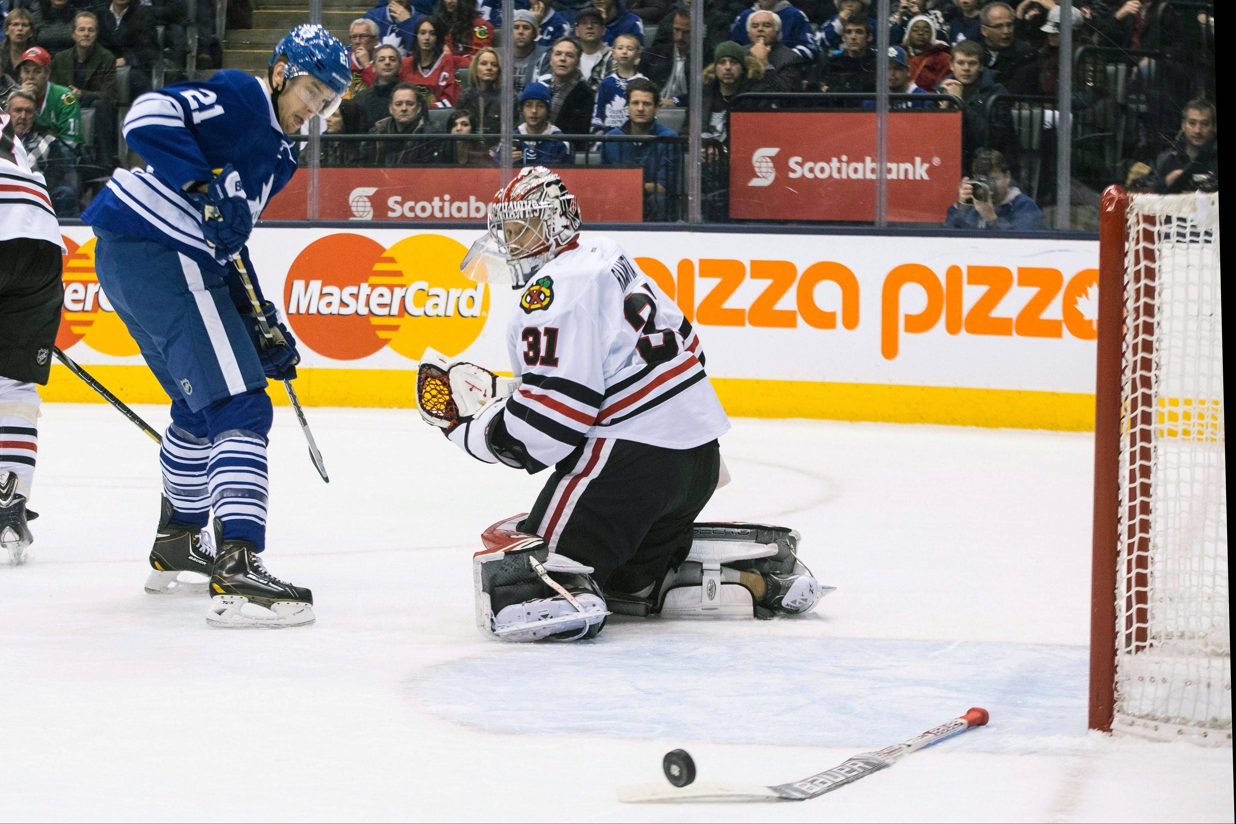 Hawks goalie Antti Raanta loses his stick as a shot by the Leafs James van Riemsdyk slides wide of the net Saturday night in Toronto.
