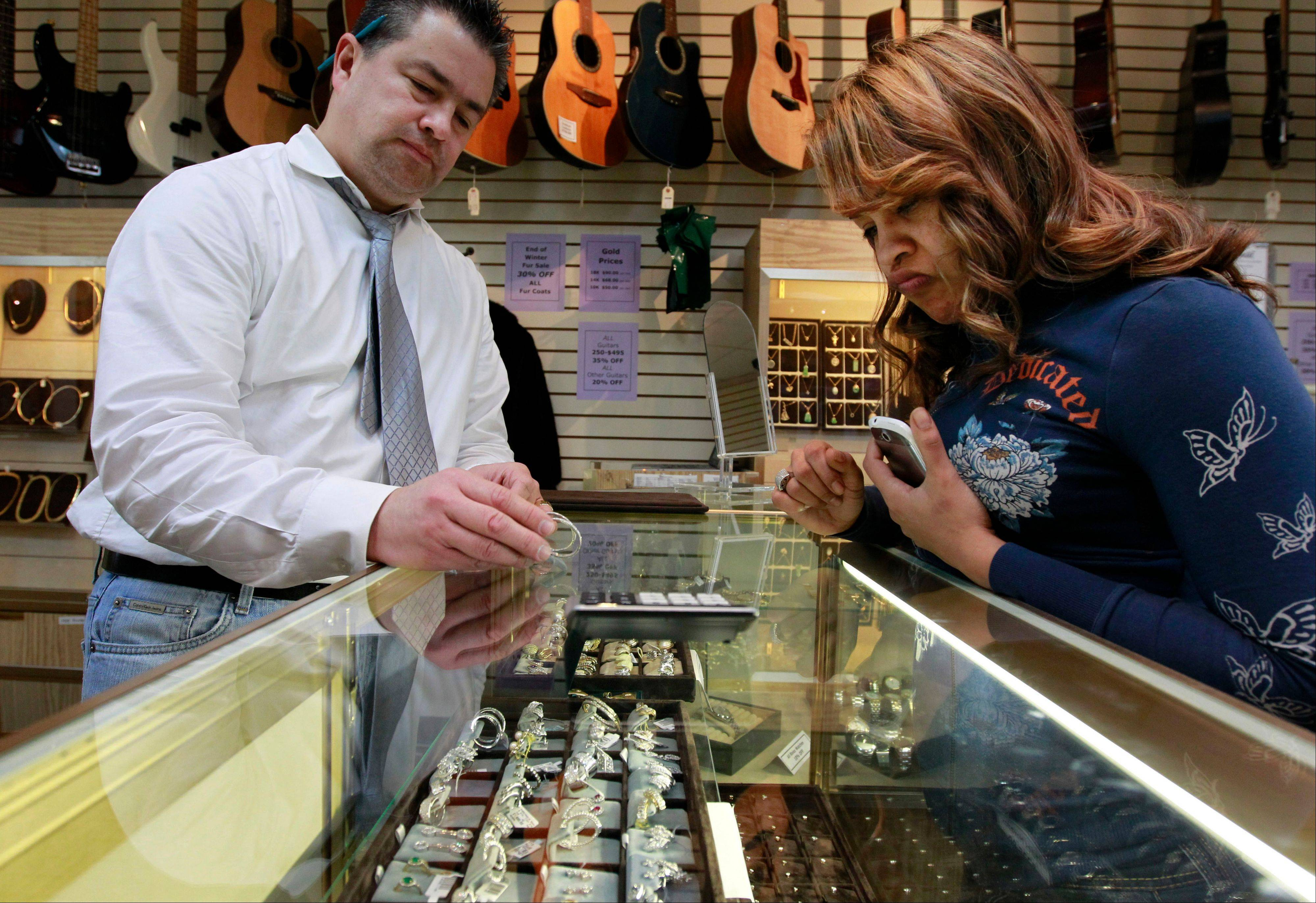 Loan officer and salesman Roy Knudsen, of Boston, left, displays earrings to Doreena Ruiz, of Framingham, Mass., as Ruiz shops at Suffolk Jewelers & Pawnbrokers, in Boston, Tuesday, Nov. 22, 2011. Pawnshop are emerging from the shadows. As access to credit remains tight, a growing number of borrowers are getting cash by pawning their jewelry, electronics and other valuables.